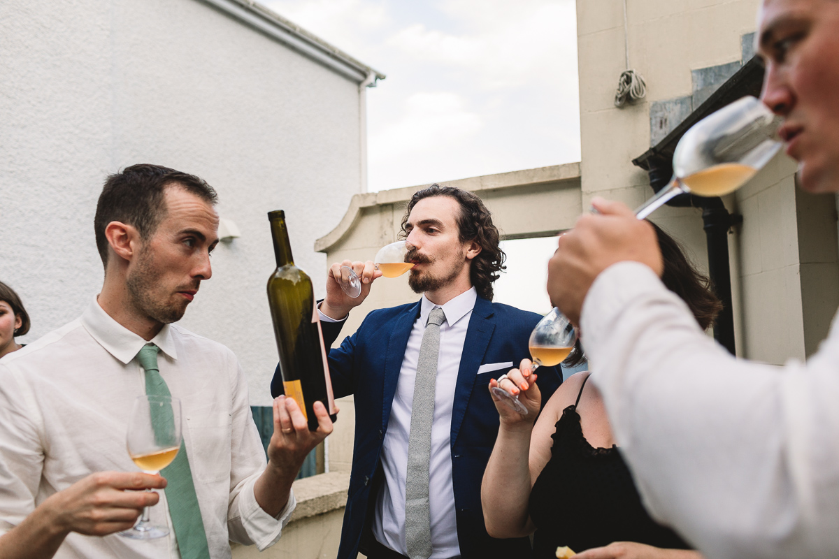 Group of wedding guests sampling wine at fun and quirky village hall wedding in Shropshire
