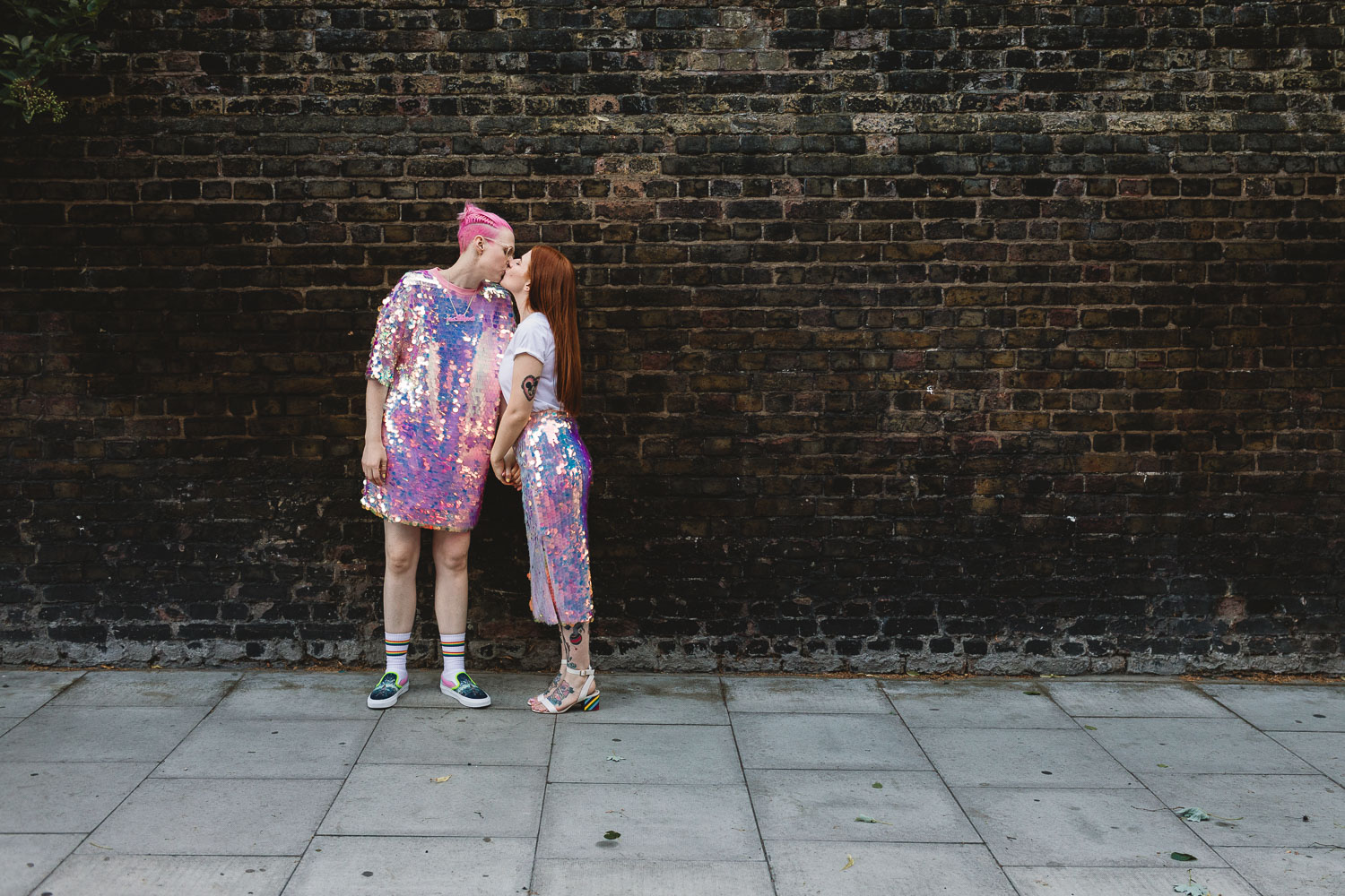 Same sex wedding, two brides fun sequin outfits kissing, one has pink hair and the other tattoos stood by a brick wall in Hackney outside The Old Dairy in London