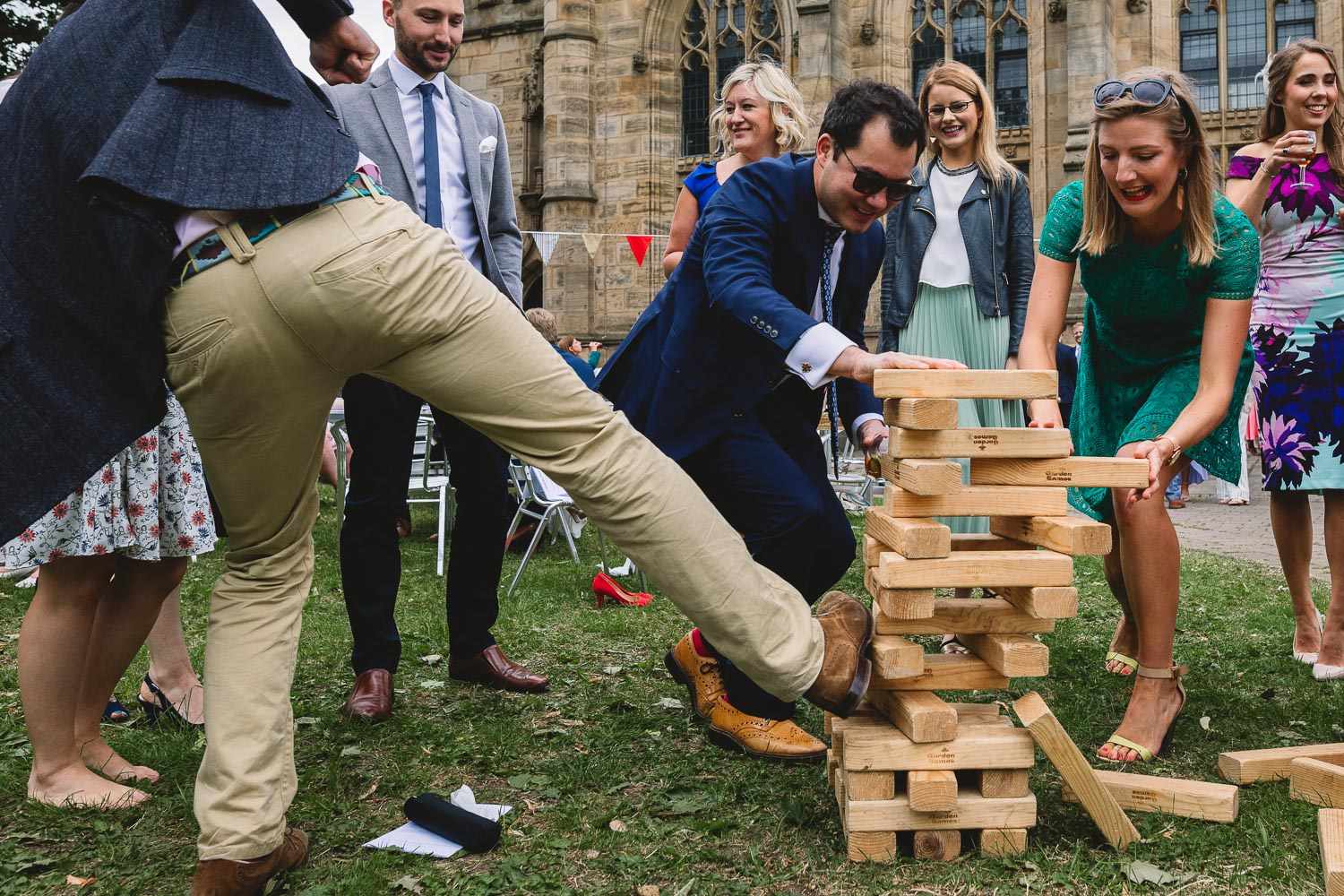 Fun photo of guests playing giant jenga lawn games and one guest is trying to kick the jenga over whilst the others try to keep it tall at fun 92 Burton Road Sheffield wedding