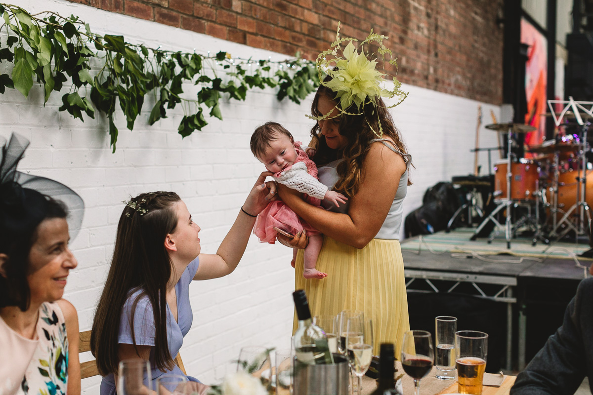 Bridesmaid in lilac dress sitting at rustic table stroking a babe in arms face, in the background there is white painted  and brickwork and green foliage. Taken at 92 burton road warehouse sheffield wedding
