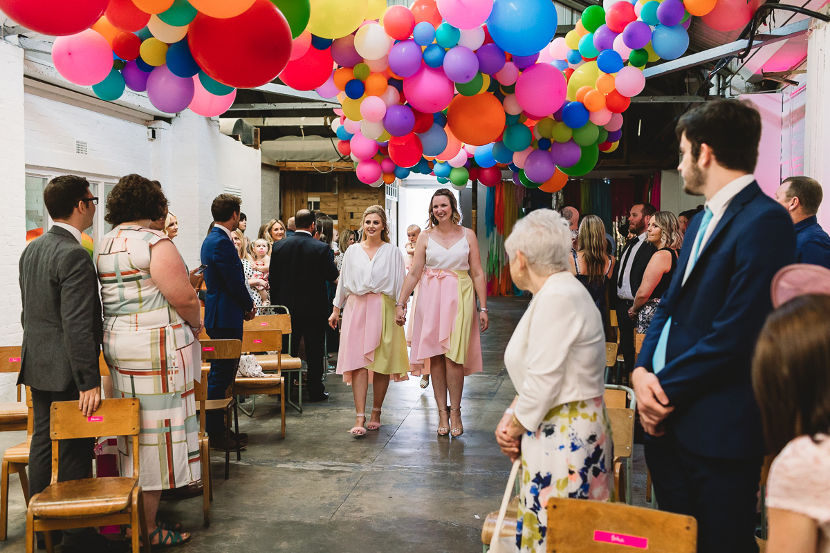 A white brick work industrial warehouse with hundreds of fun colourful balloons on the ceiling, guests are standing watching two bridesmaids in pastel yellow and pink skirts walk down the aisle at same sex Hackney wedding in London