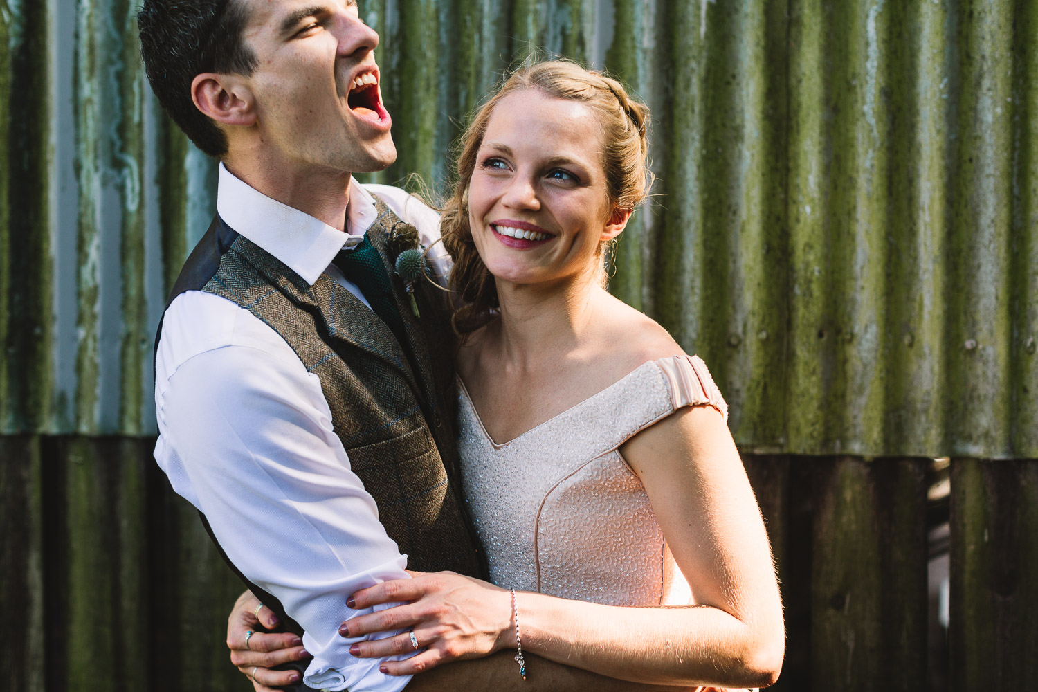 Fun looking couple embracing each other, the groom looks like he is singing and the bride is laughing. They are stood in front of a rustic rusty barn at a festival wedding in Sheffield. Bride wears a blush sequin top and groom is wearing a tweed waistcoat.