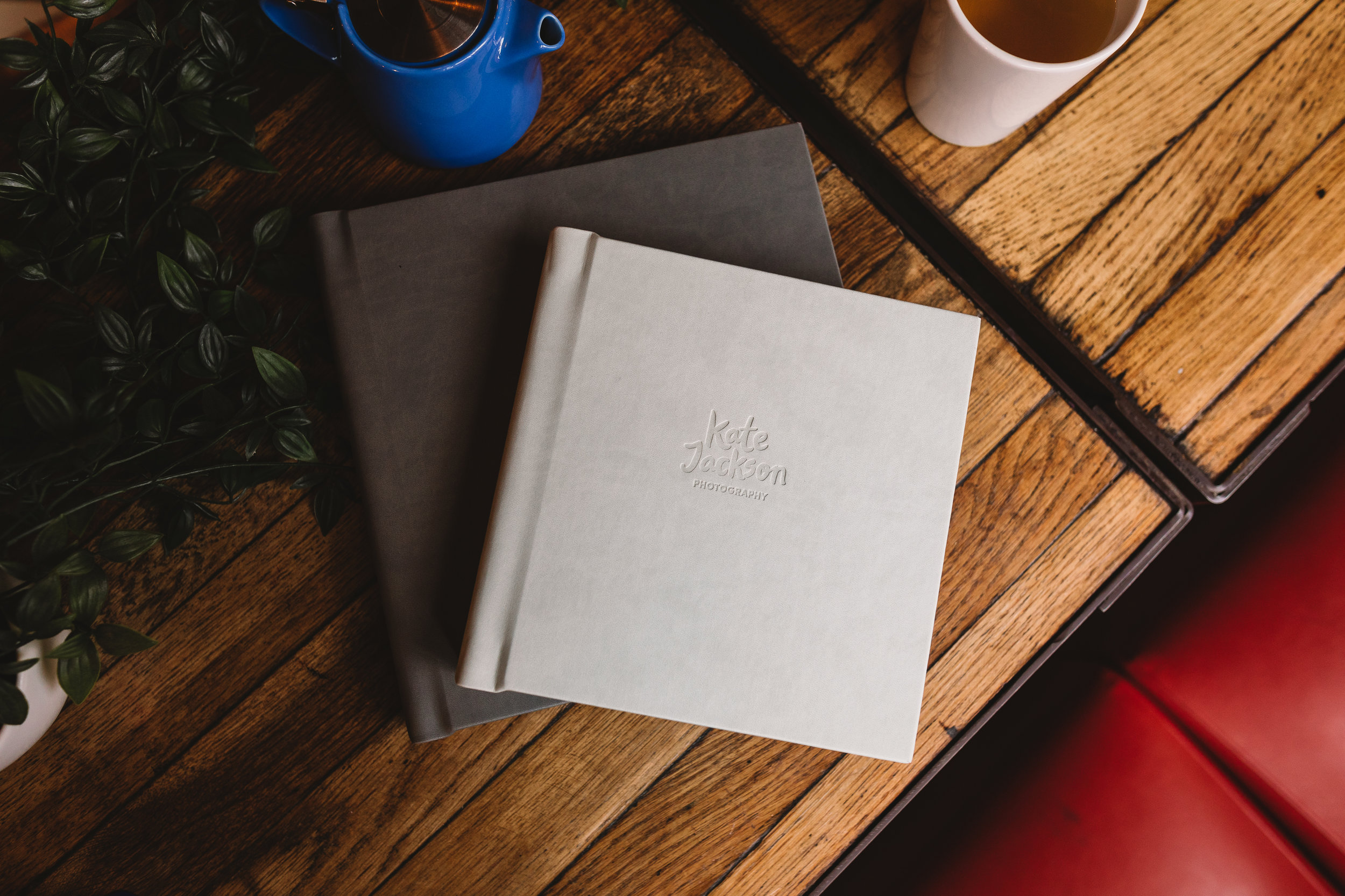 Photo of Kate Jackson Photography wedding albums on a wooden table with a cup of tea and quirky tea blue teapot.