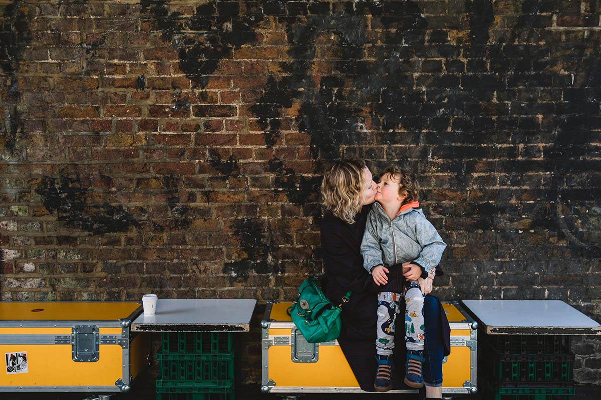 An urban brick wall and yellow hard cases used for seats with green crates as tables against a brick wall, a mother with blond shoulder length curly hair has her toddler on her lap and he is giving her a kiss. Photo taken on documentary family shoot in London.