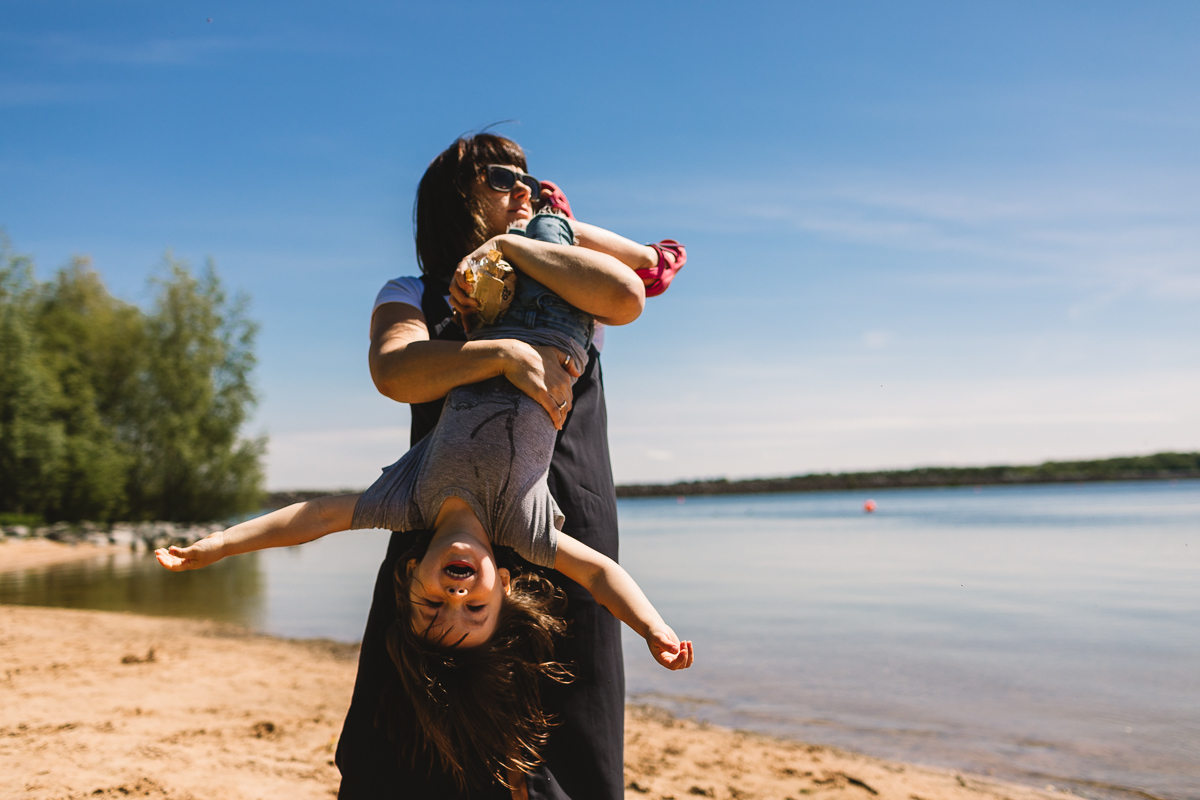 Photo taken at Rutland Water of a mother holding her 3 year old upside down and walking a long the beach at the edge of the water, the sky is very blue and it's a bright summer day. Photo taken on documentary family shoot by Birmingham Photographer Kate Jackson