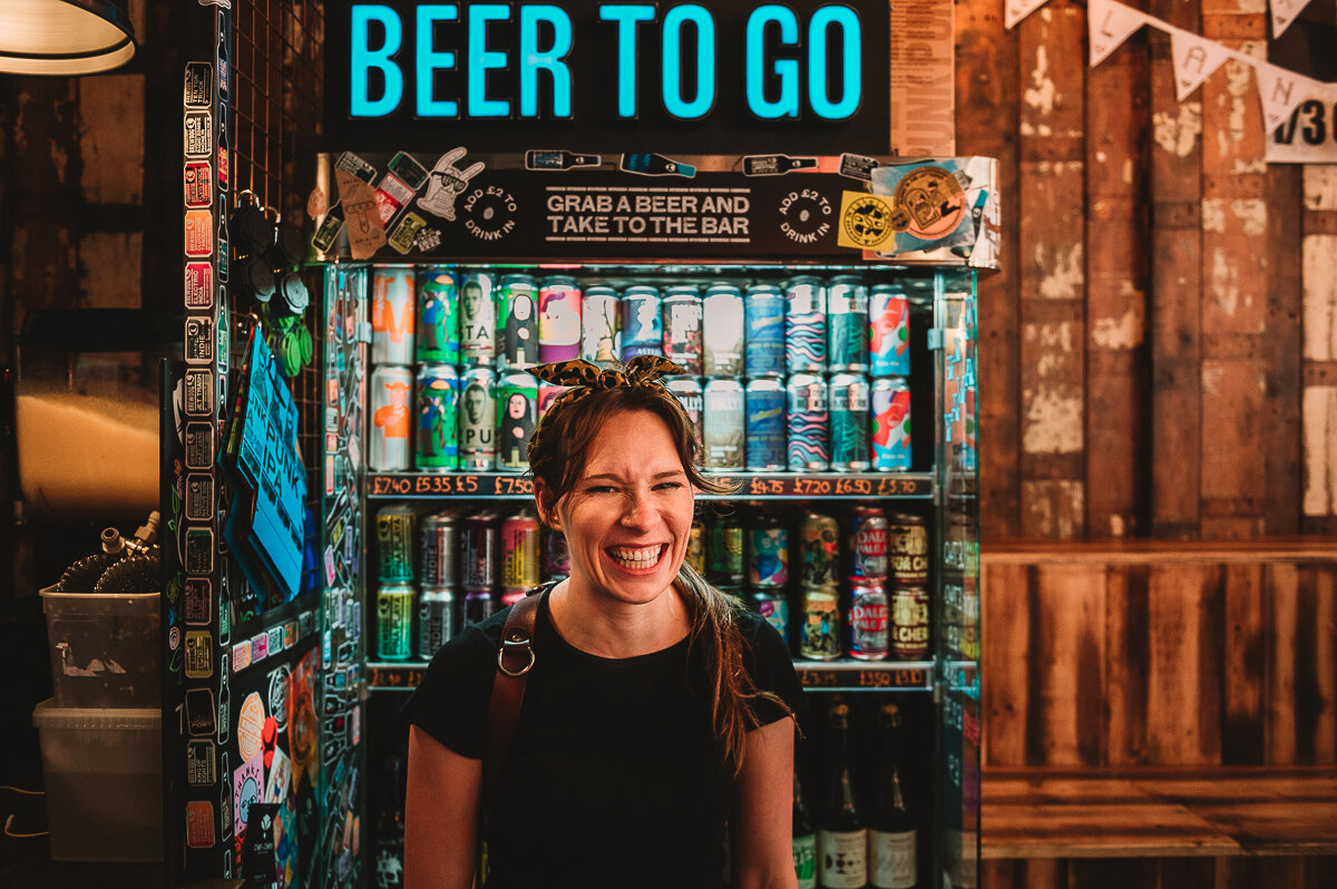 Photo of Kate Jackson Photography at a wedding in Brewdog, she is stood in front of a colourful beer fridge with a sign saying BEER TO GO and is laughing having fun.
