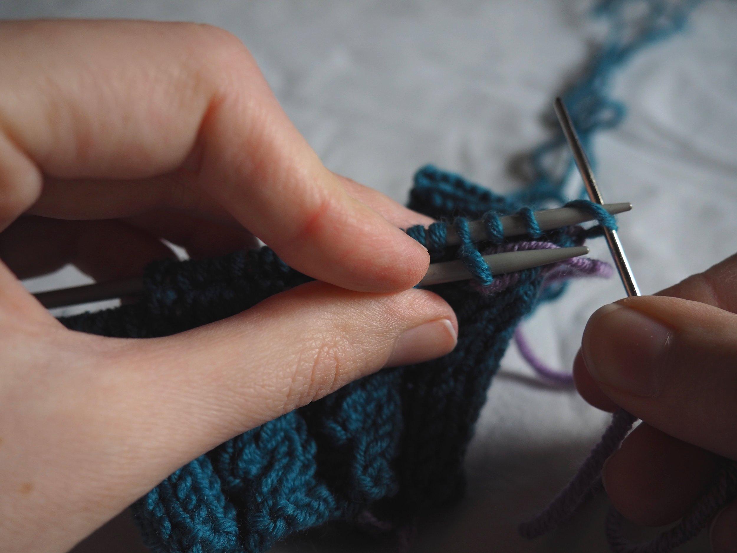Aiguille 2  : Insérez l'aiguille à laine dans le 1è maille comme pour faire une maille endroit et faites la glisser de l'aiguille,