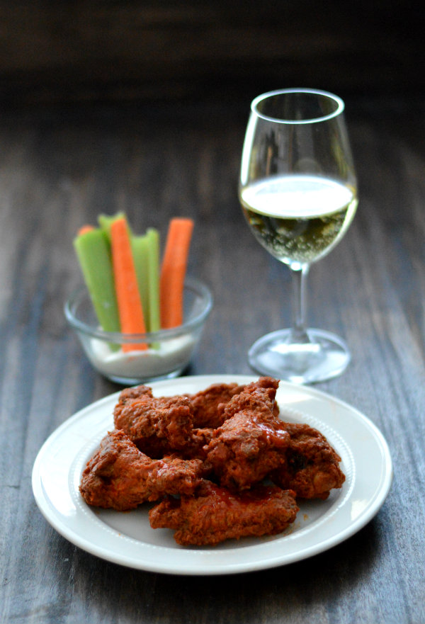 Chicken Wings can be a tough dish for wine pairing, but there are some wines that work! Dani from Care to Pair lists out what your wine needs to have in order to pair with sweet or spicy chicken wings | CaretoPair.com