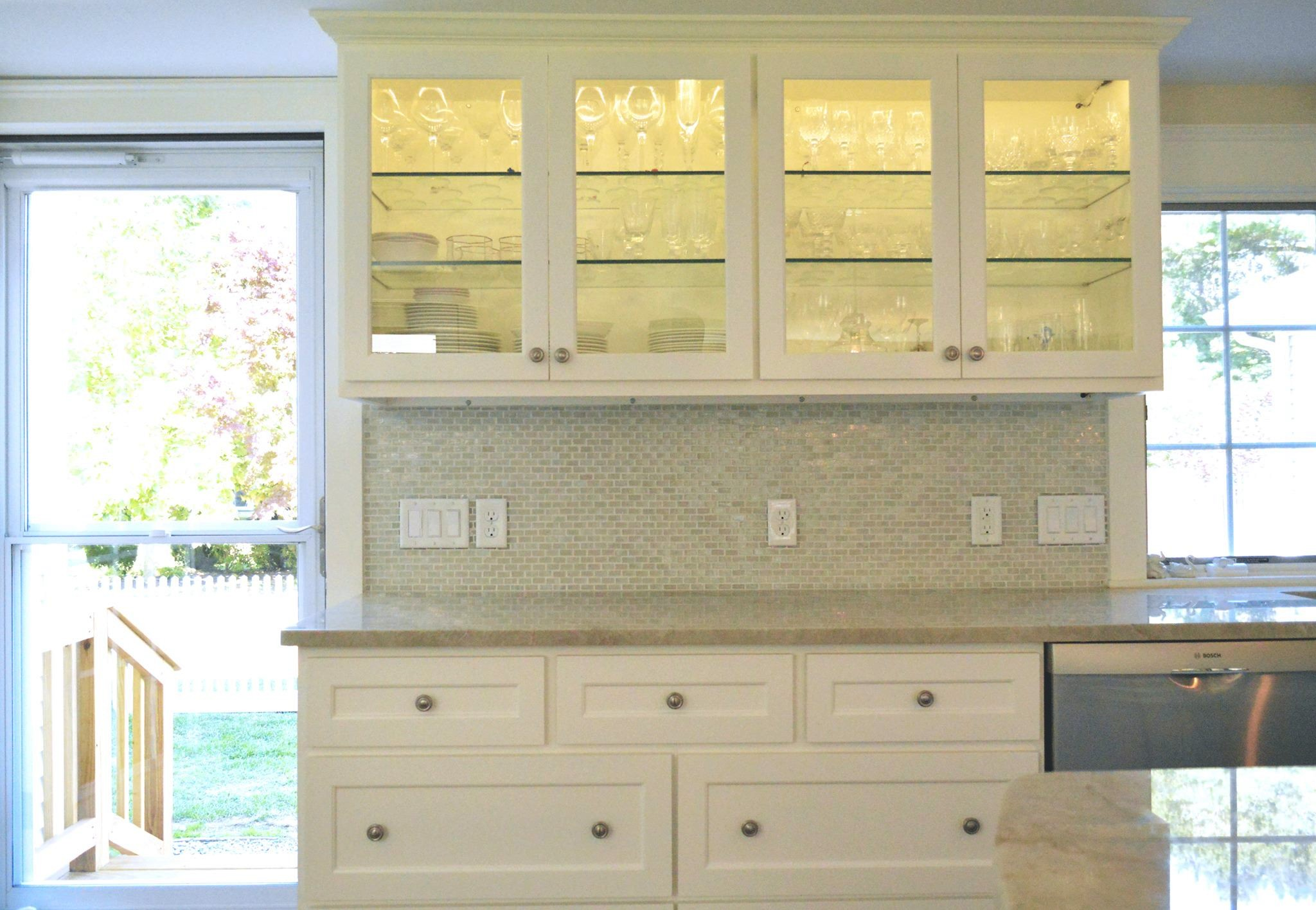 Glass cabinets with interior lighting showcase the client's stemware collection.jpg