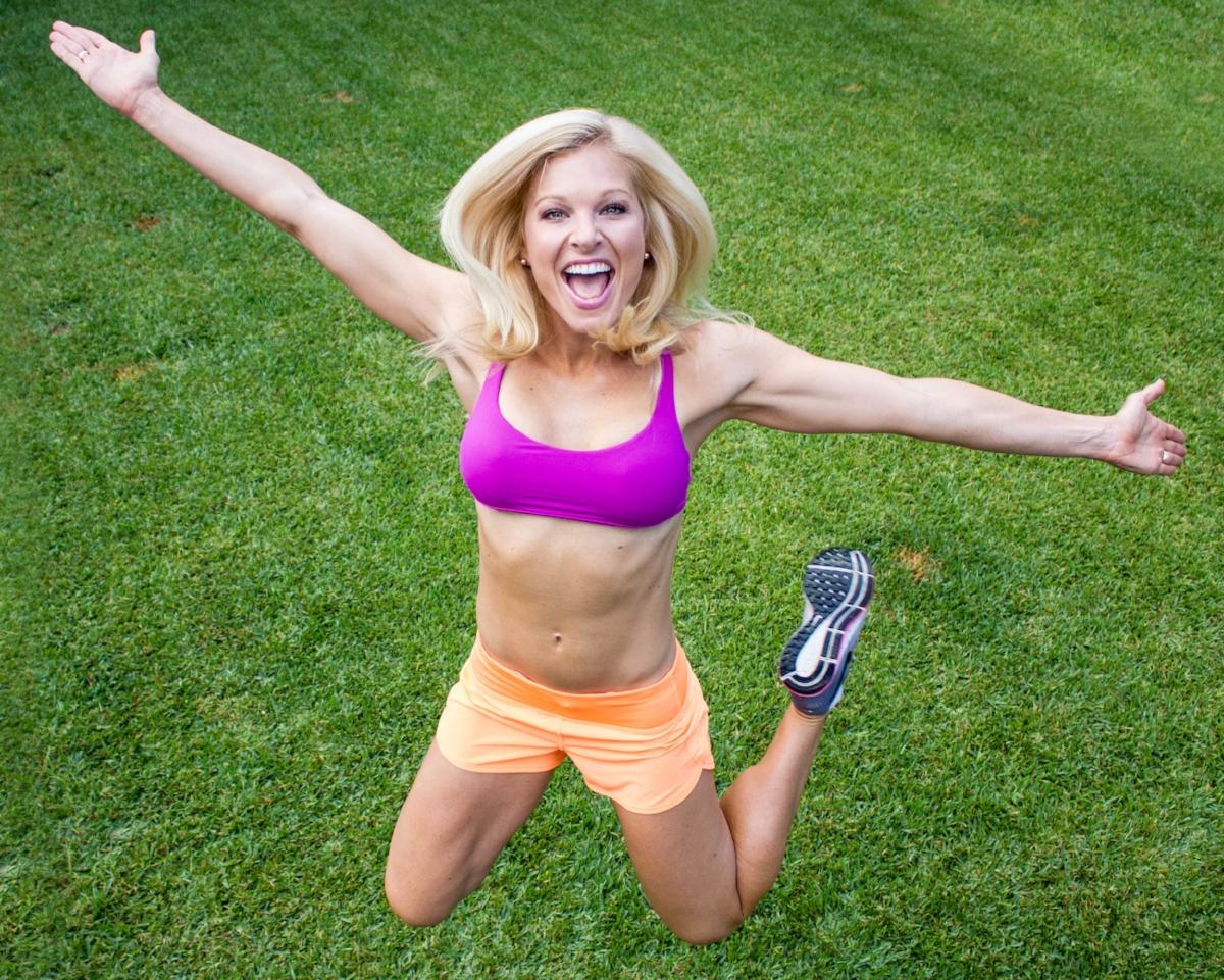 ACTION ANNA fucshia sports bra, orange shorts, green grass.jpg