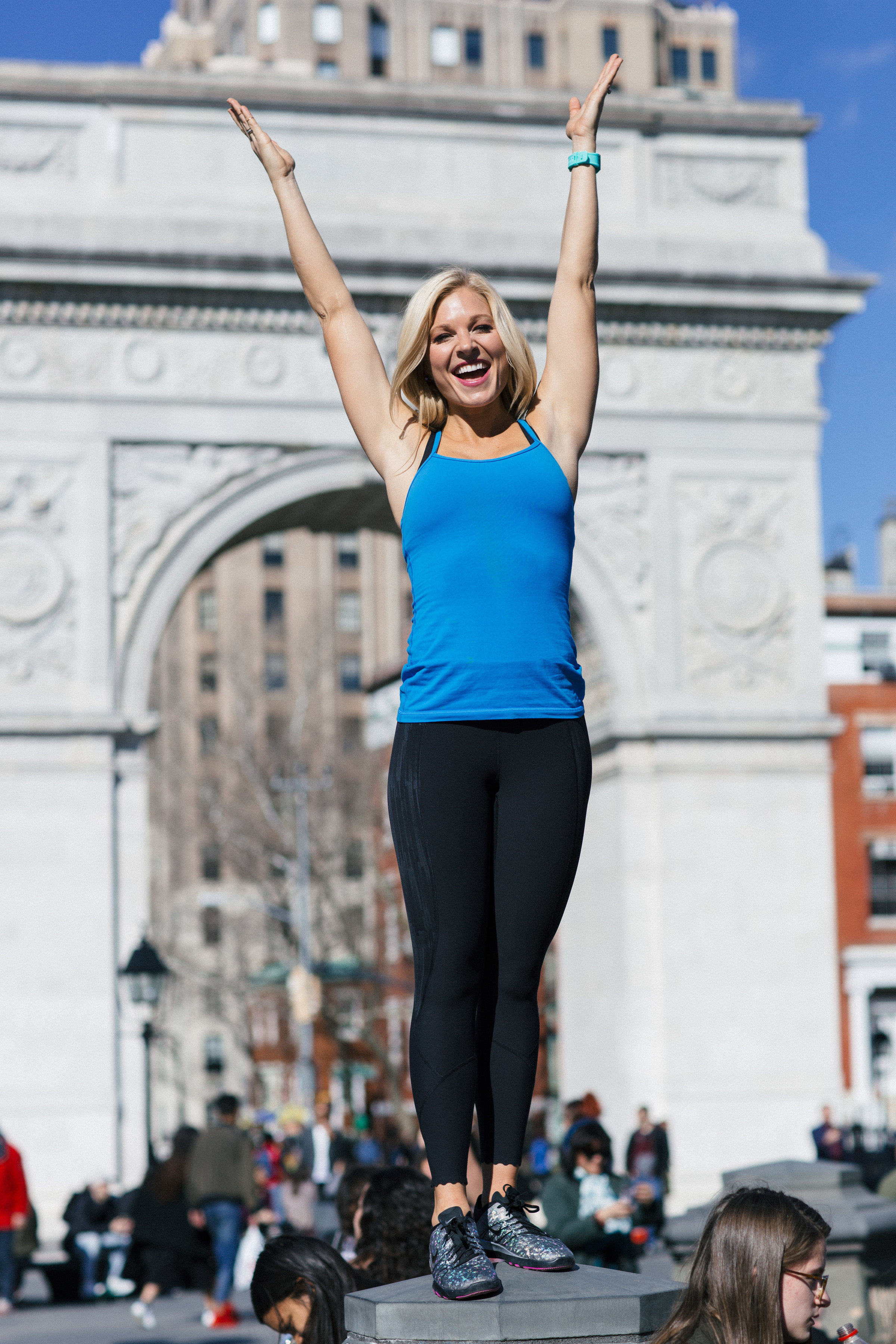 Anna Kooiman New York City Washington Square Park Standing on Fountain arms up Lululemon Nike fitness fashion Lydia Hudgens