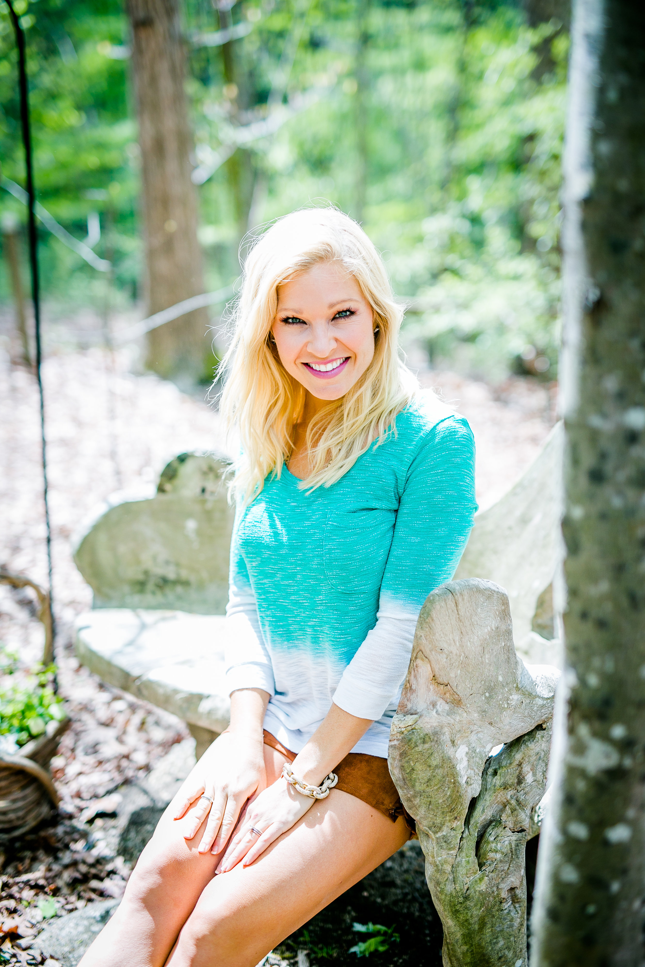 Anna Kooiman seated wooden bench in north carolina woods teal top brown shorts eben adrian patten