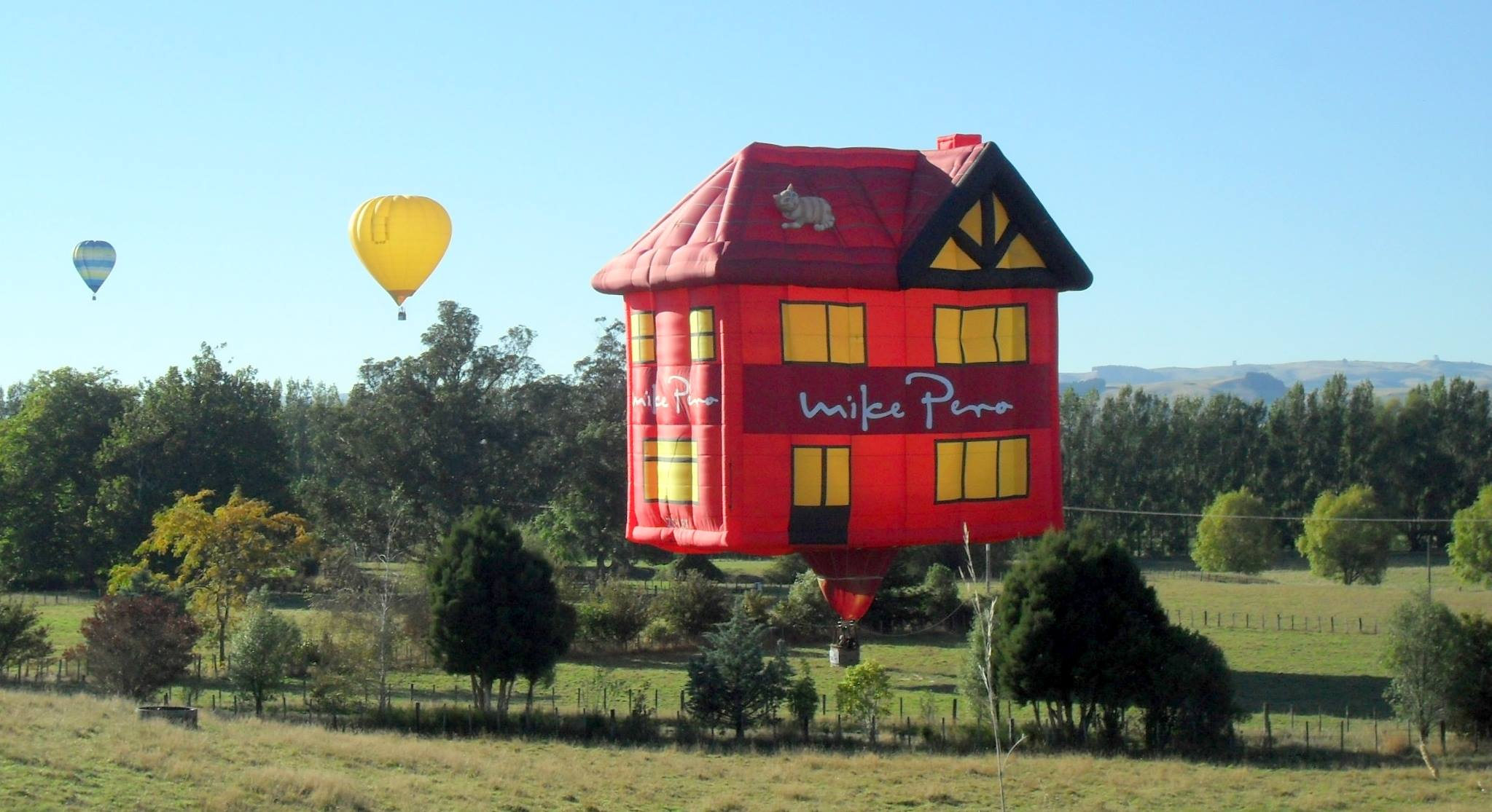 Mike Pero House (ZK-LBT)    McKee, Daryl   A flying house balloon owned by Mike Pero Real Estate will be an unmissable sight with its bright red walls and pointed 'roof' with a cat napping on top.  NOT for Sale ...  Wairarapa Balloon Festival  is delighted to welcome a flying house as our second special shape to this year's 20th Celebrations ... Thank you Mike Pero