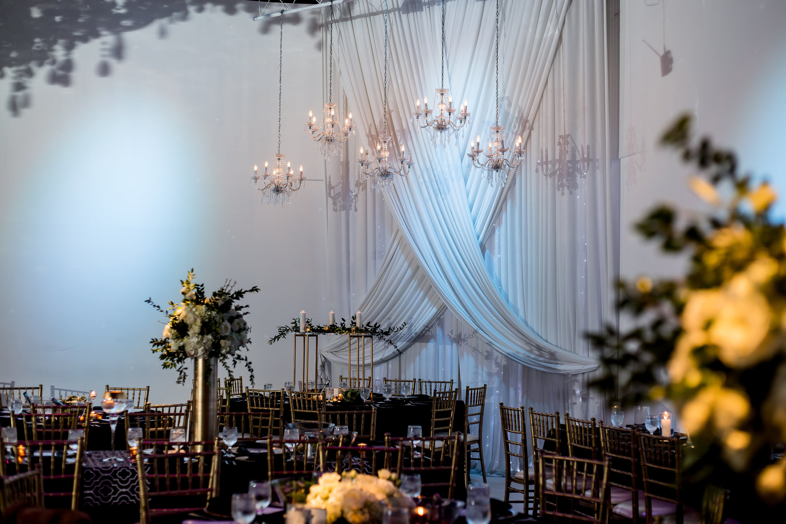 A shot of Amanda's reception decor—She built those gold rectangle towers, added a marble topper, and supplied the candles!