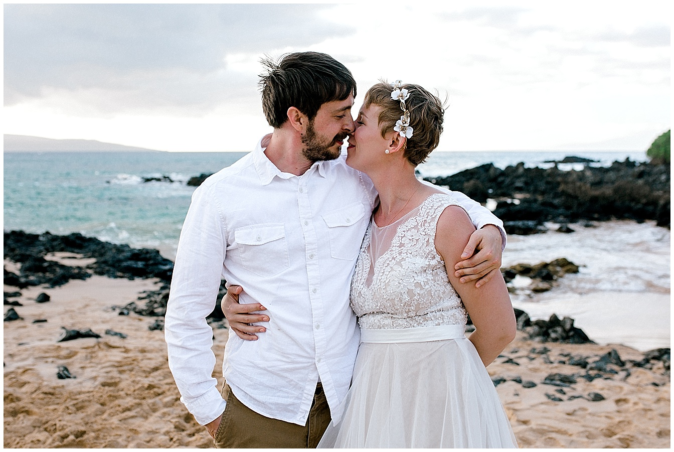 Bride and groom embracing on Maui beach