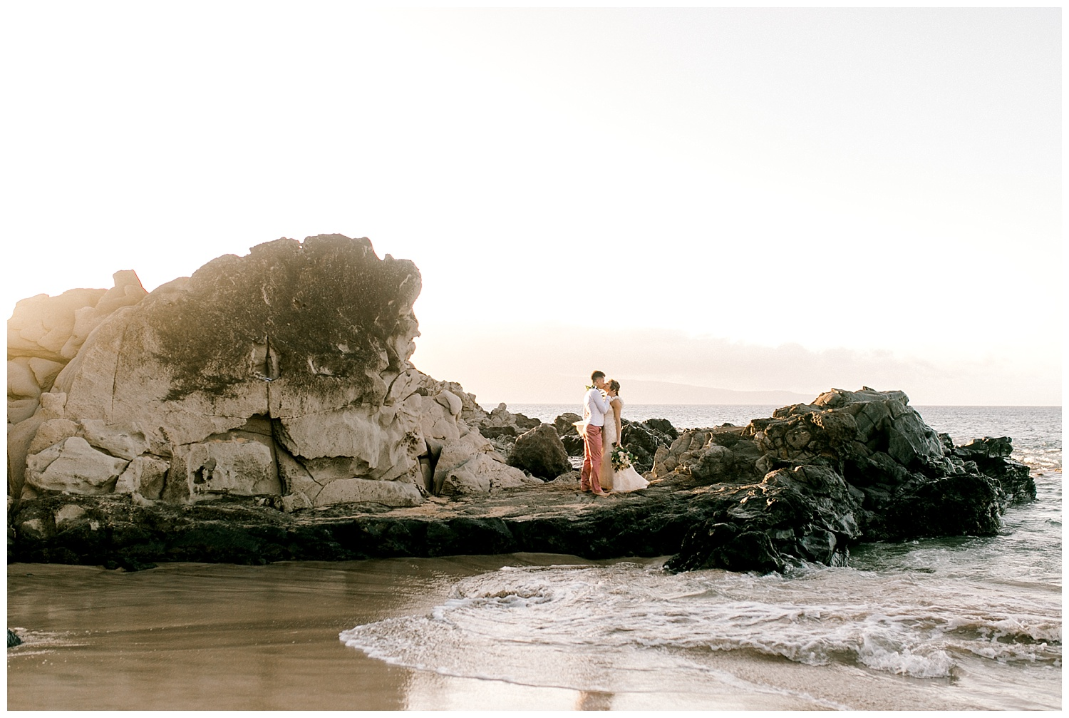 Bride and groom on lava rocks on Maui beach