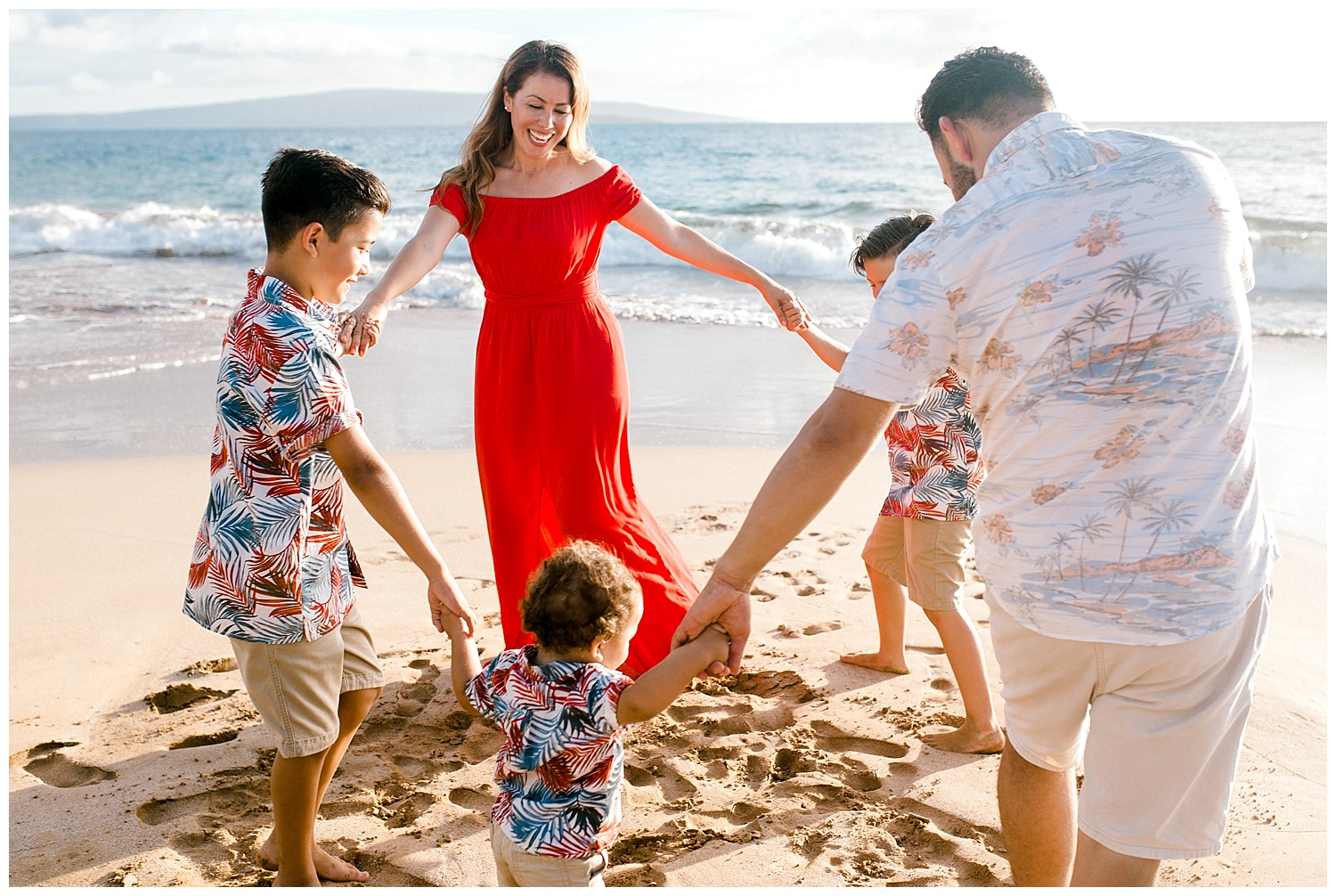 Family playing Ring Around the Rosie on a Maui beach