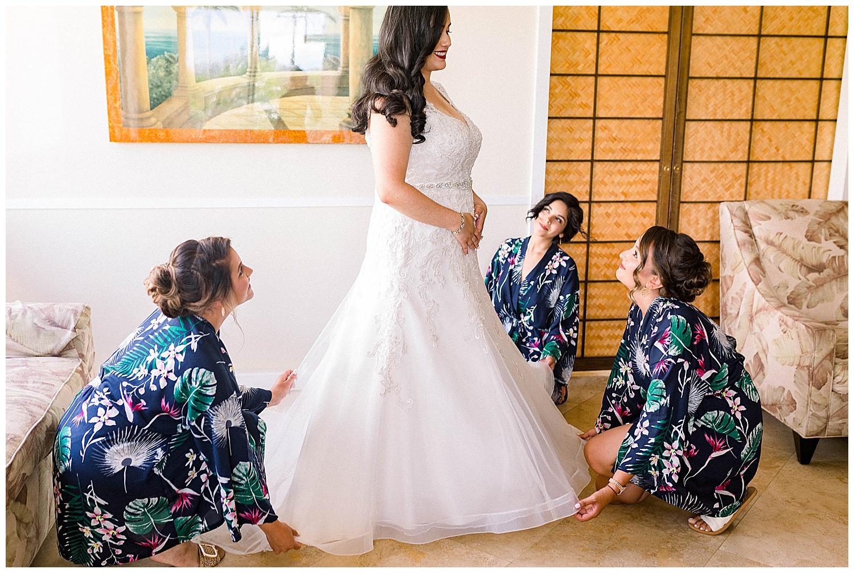 Bridesmaids helping bride get into dress in Kihei, Maui