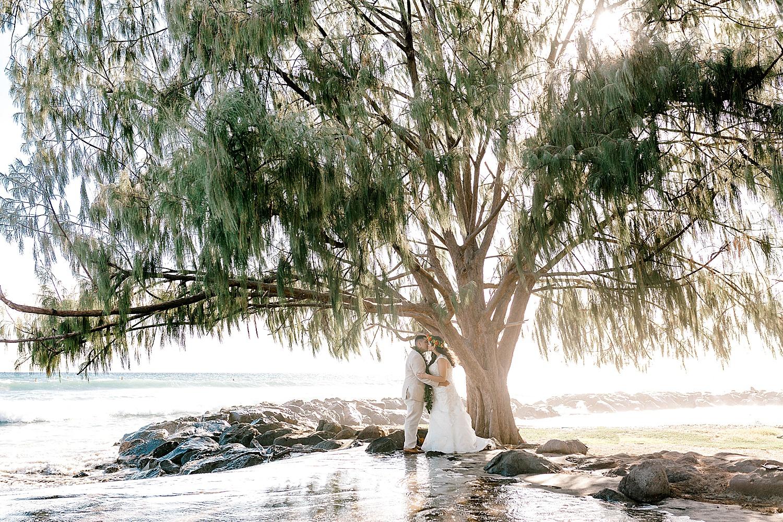 Bride and groom kissing at Launiupoko Beach