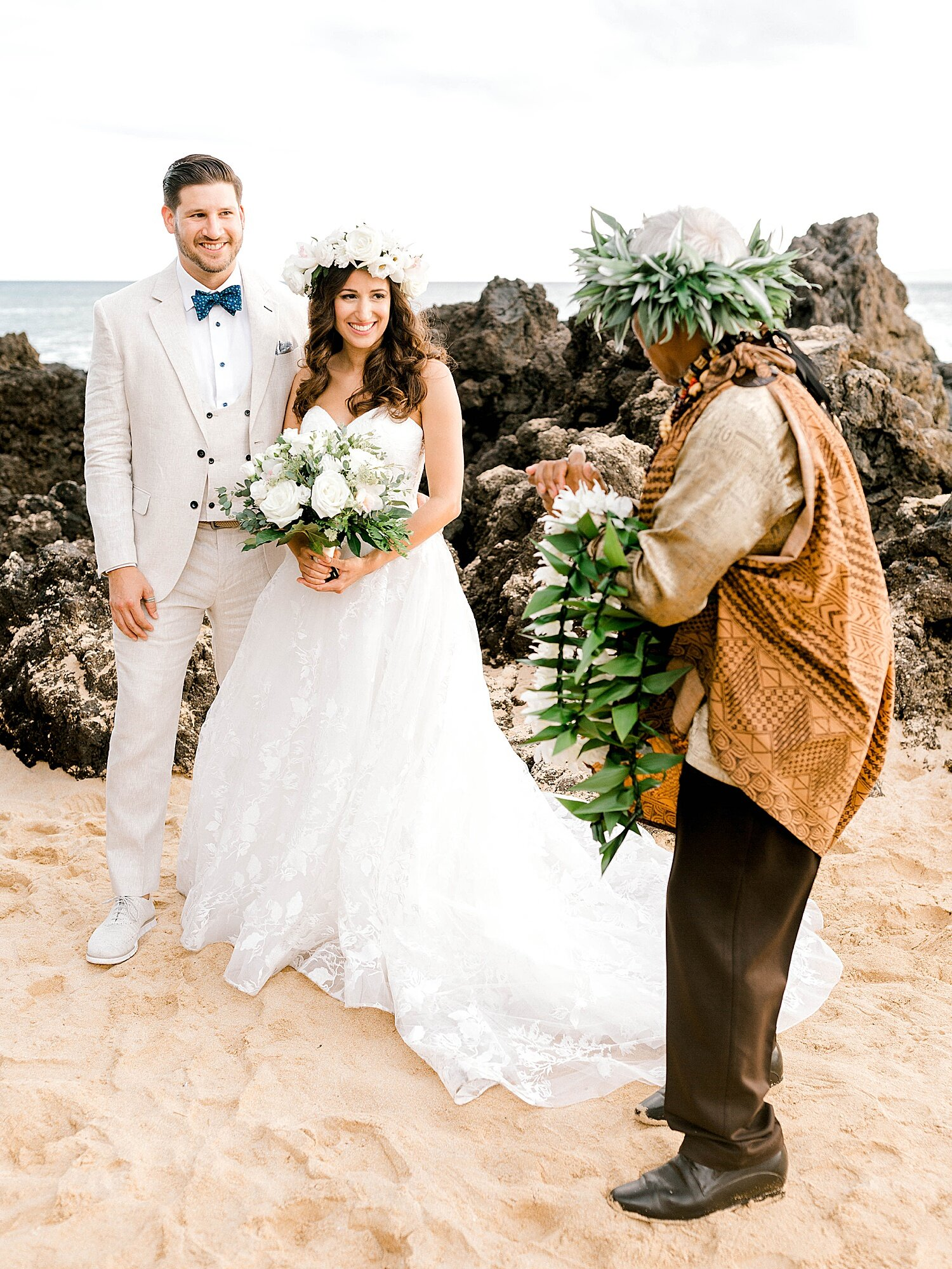 Bride and groom standing on Maui beach at the start of a Hawaiian wedding ceremony