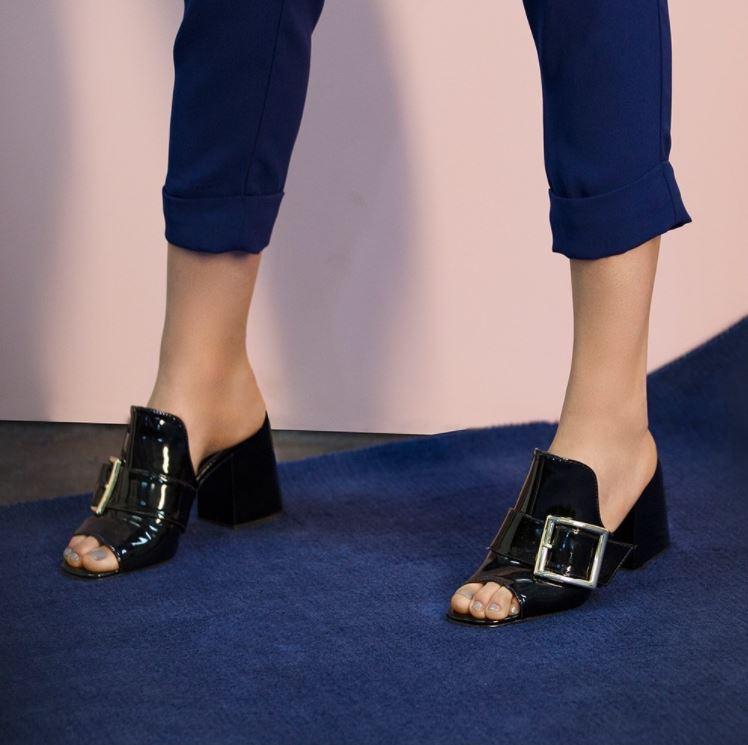 Modelo calçando mule com salto preta AMARO e calça azul cropped.