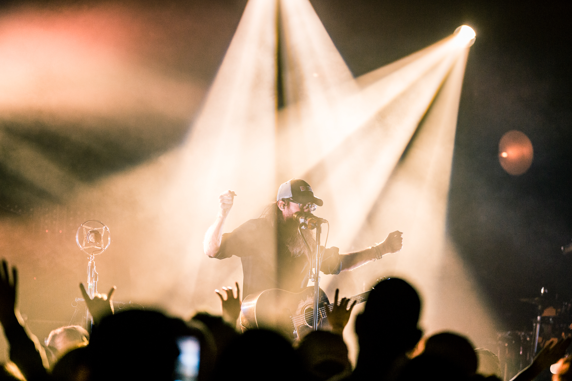 Concert photography is all about waiting for the right moment. While I think this photo has a lot of great elements to it (overall composition, lighting, subject, foreground crowd) I think the photo below is stronger.