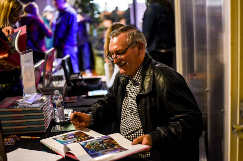 Dick Evans signs books at  The Mission  book launch party on April 13, 2017
