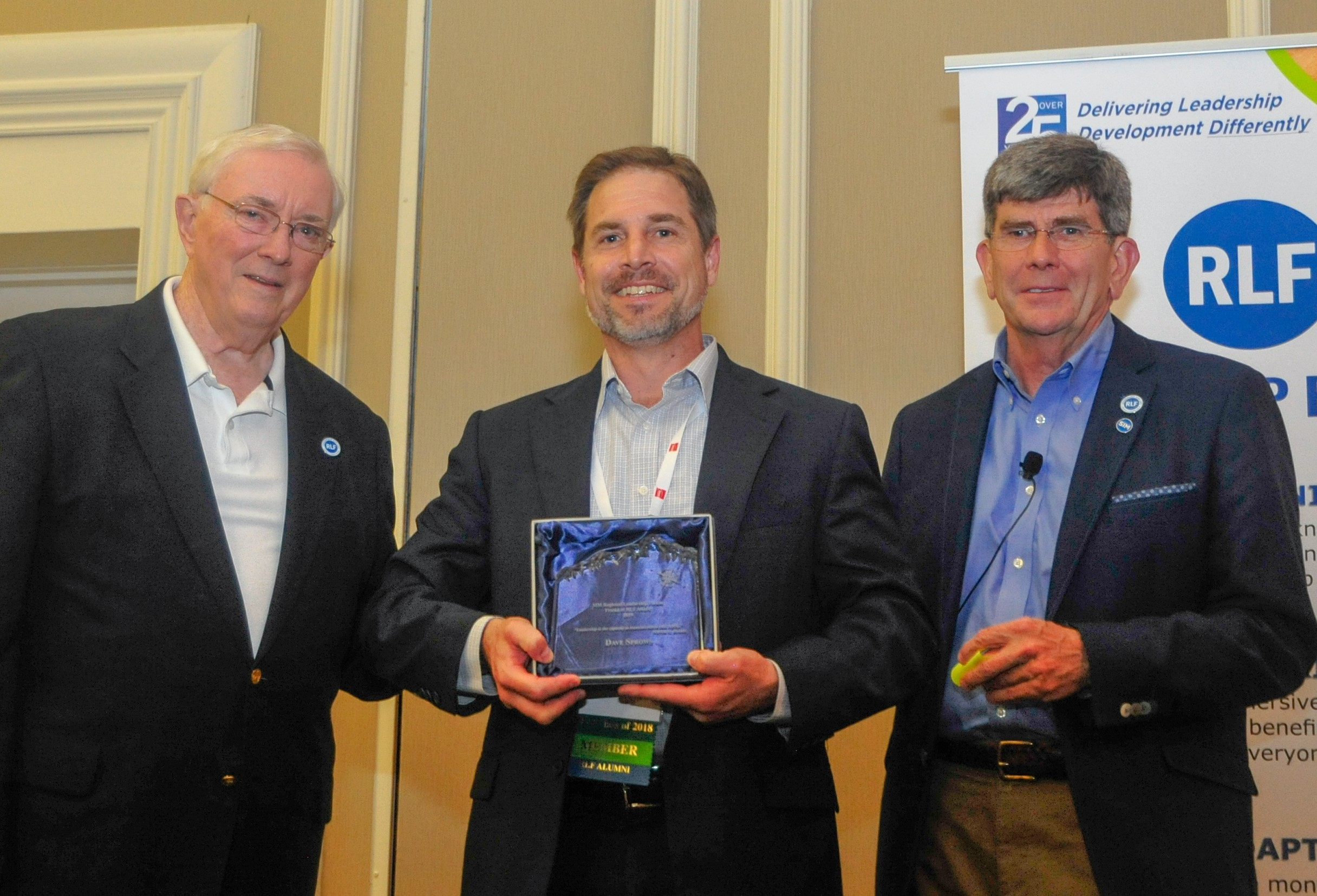"Two ""Friend of RLF"" awards were presented on May 15, 2019 during SIM Connect Live. Above, Northeast RLF facilitators Bart Bolton (left) and Kevin Ryan (right) present a ""Friend of RLF"" award for Dave Sprows of Wellington Management — accepted on Dave's behalf by his Wellington colleague Phil Hattwick. Pat Randall of Kforce also was presented with a ""Friend of RLF"" award during the event."