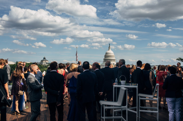 Event attendees socializing on rooftop deck, with Capitol building in background