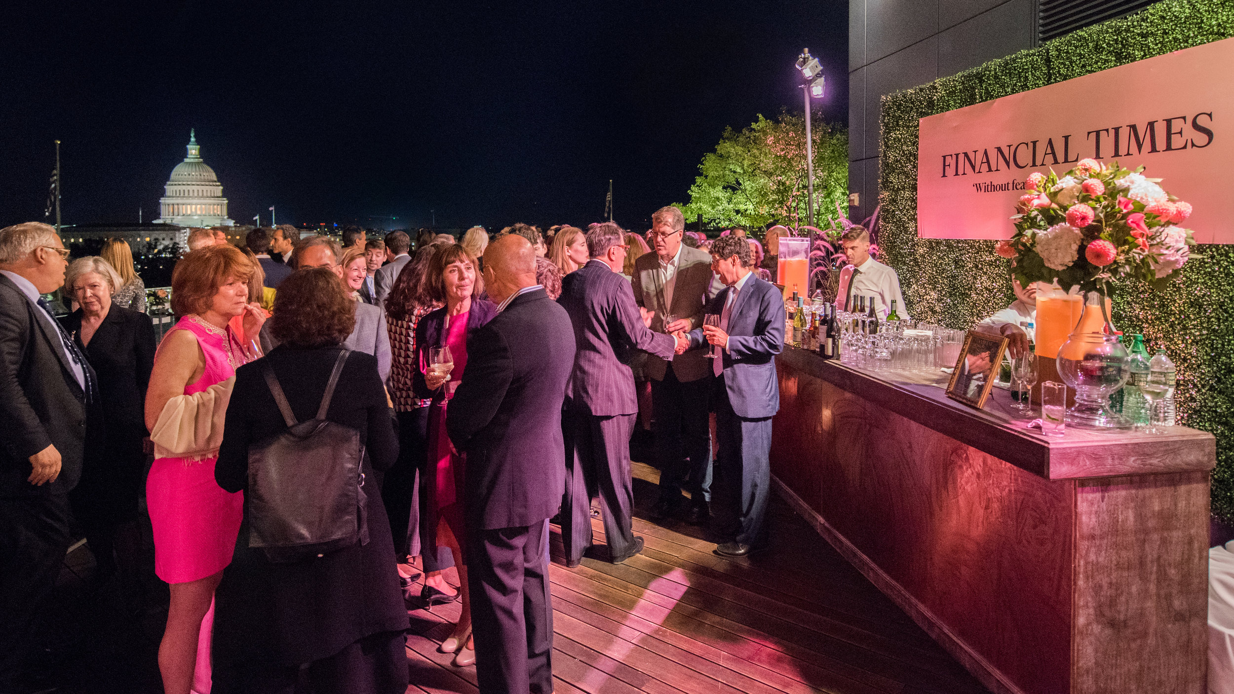 Event attendees socializing near a bar on the rooftop space, with the Capitol building in the background