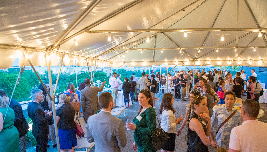 Event attendees socializing in tented rooftop space