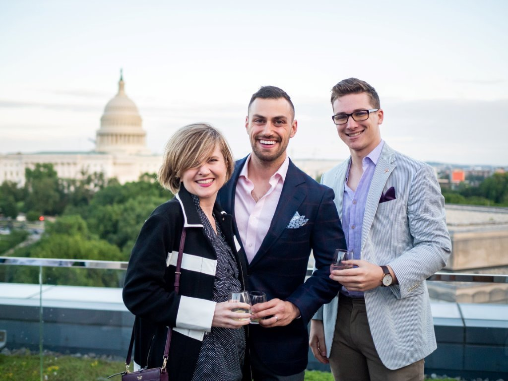 A woman and two men posing for photo, with Capitol building in background