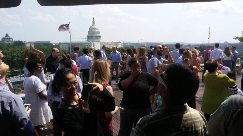 Event crowd socializing, with Capitol building in background