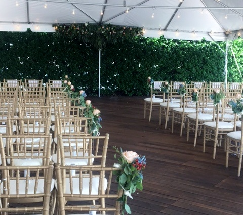 Wedding space seating, aisle, and floral arrangements in tented area