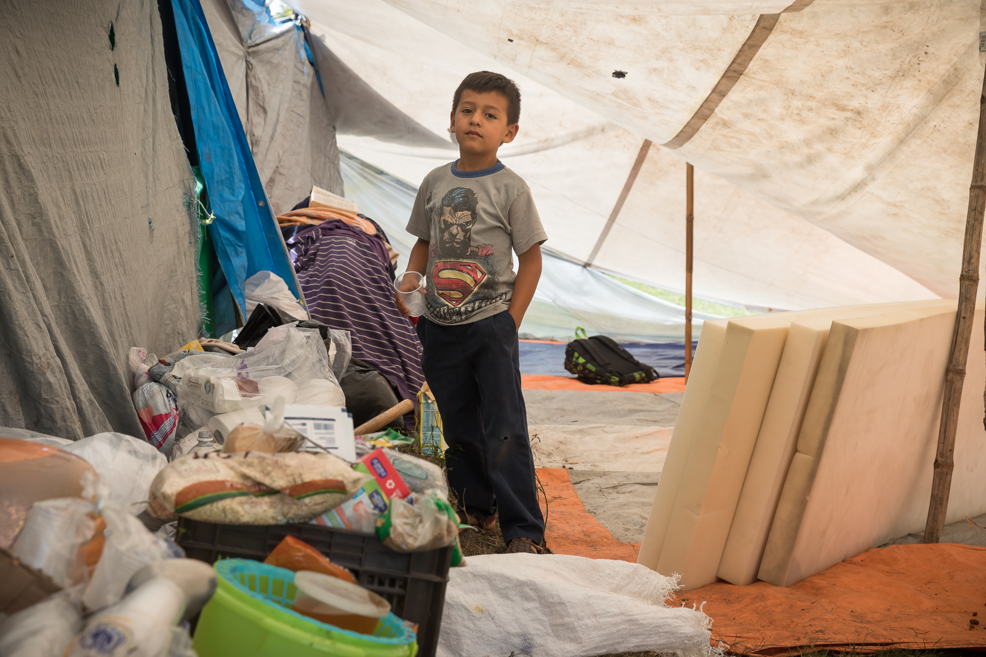 Jorge Martínez Aponte, 7 years old, went from living in a cosy home one day to living with his family and other 8 families in a makeshift tent refuge the next. PHOTO: Francisco Alcala Torreslanda