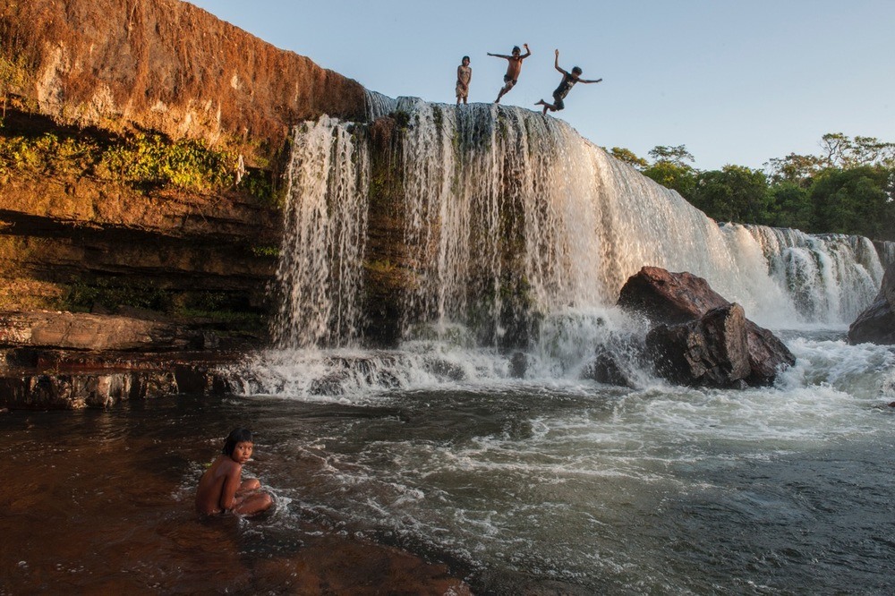 CHILDREN OF THE KAYAPO TRIBE LEAP OFF A WATERFALL.  PHOTO: CRISTINA MITTERMEIER