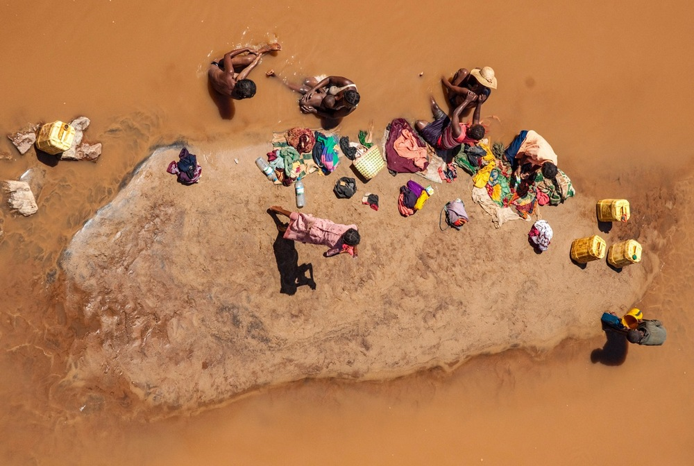 A FAMILY WASHES AND BATHES IN THE WATERS IN MADAGASCAR.  PHOTO: CRISTINA MITTERMEIER