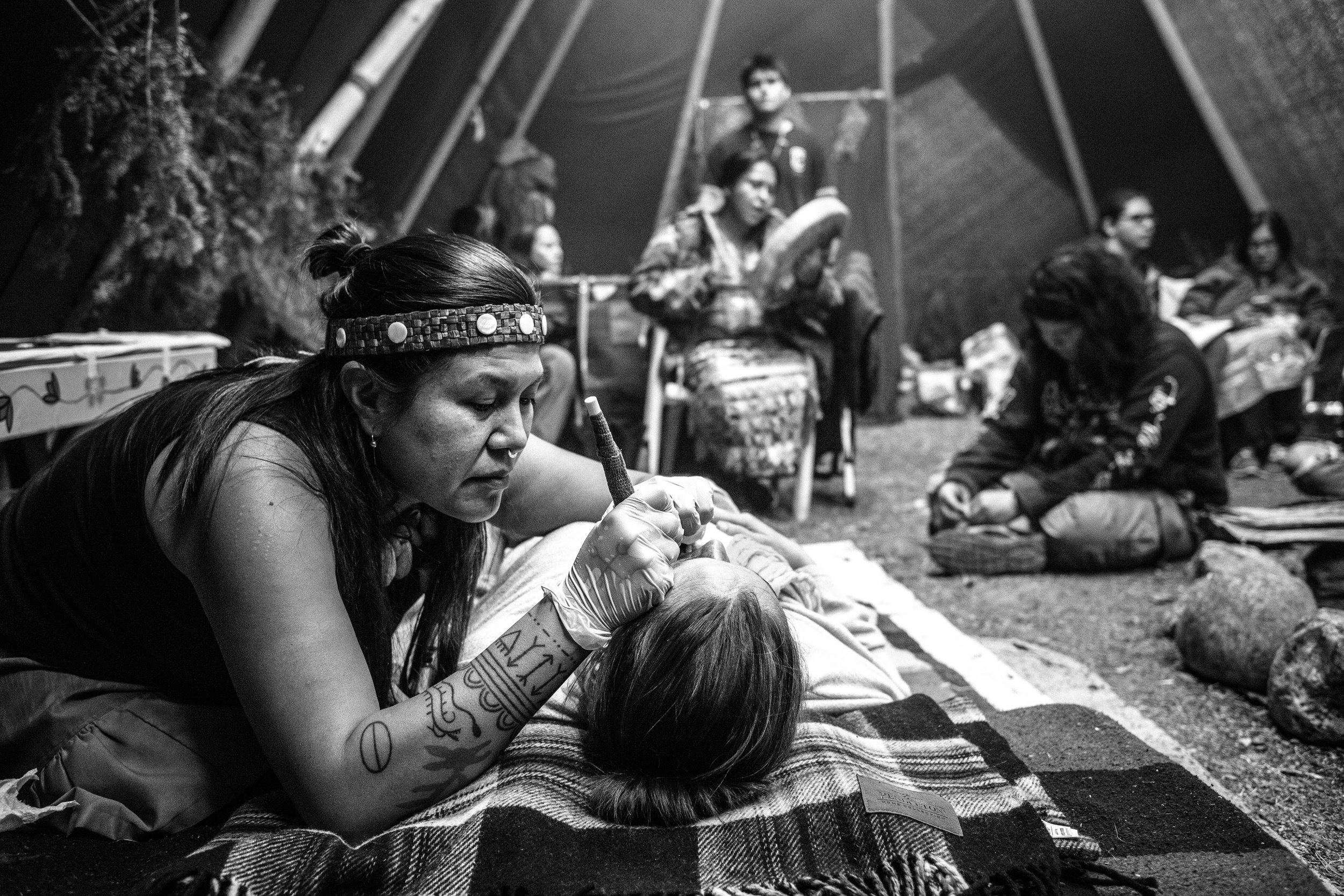 At Nimkii Aazhibikong, Indigenous people gathered on reclaimed Indigenous land to relearn and express their traditional tattoo practices.  Photo by Stan Williams
