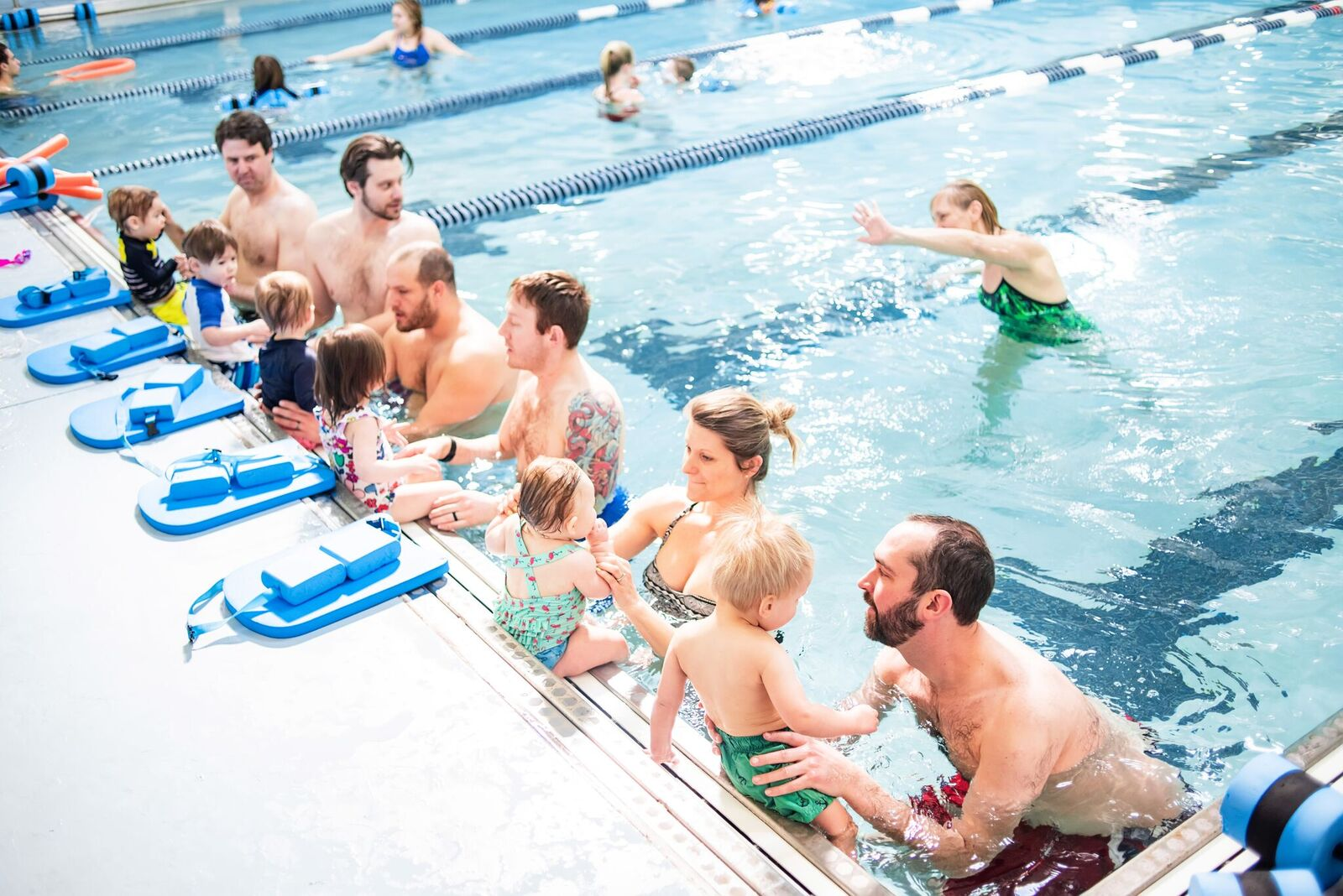 Child swimming in pool with parents