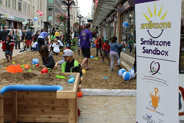 """Smilezone Foundation built a new raised sandbox component to ensure access for more kids.  The sandbox was built by UBC Local 93 volunteers using sand donated by Karson Aggregates."""