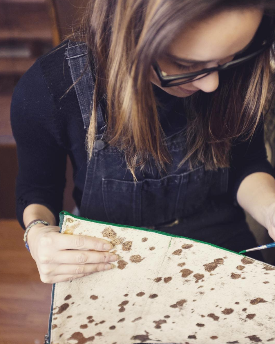 Brit Reed, Head Designer at Tesoro Design, hand-dying the edges of their bags.
