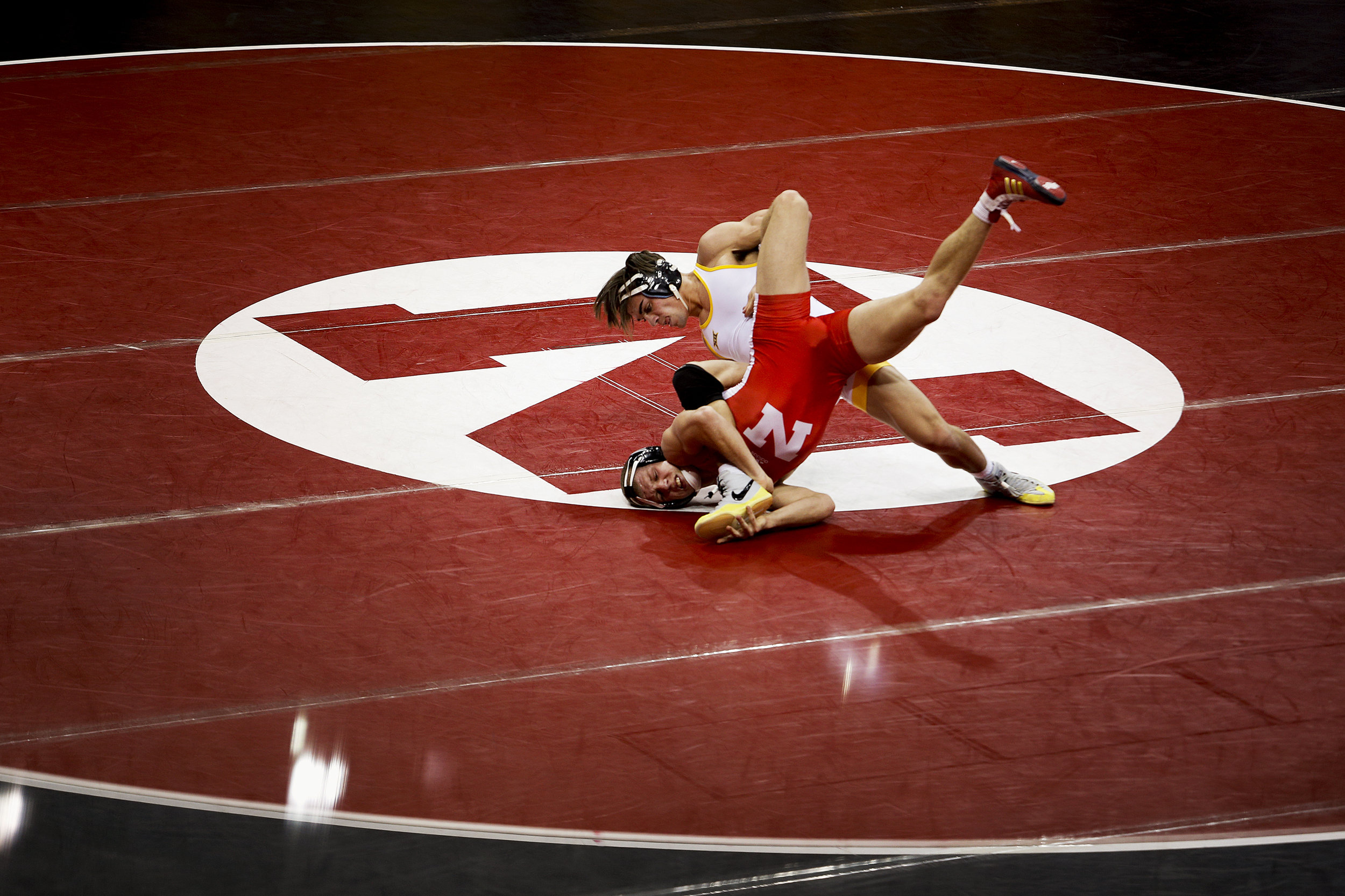 Nebraska's Anthony Abidin (red) is forced to the mat by Wyoming's Bryce Meredith (white) during their match at Devaney Sports Complex Saturday November 21, 2015 in Lincoln, Nebraska. Meredith would defeat Abidin 12-3 but represented the only Wyoming win for the day. Nebraska defeated Wyoming overall by a score of 32-4.
