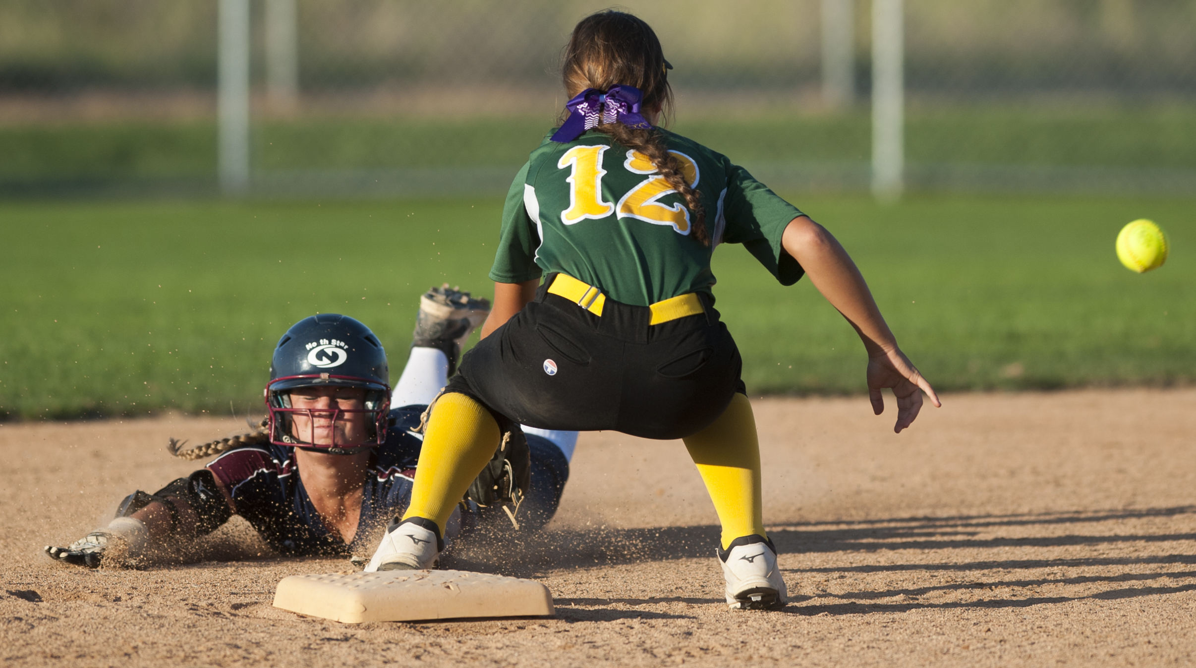 Following two errors during the play North Star's Elaina Mayer successfully slides into second base on a bunt before Pius X's MacKenzie Helman (12) can make the tag in the fifth inning of action Monday Sept. 21, 2015 at Doris Bair Softball Complex in Lincoln. Pius X shut out North Star 11-0.