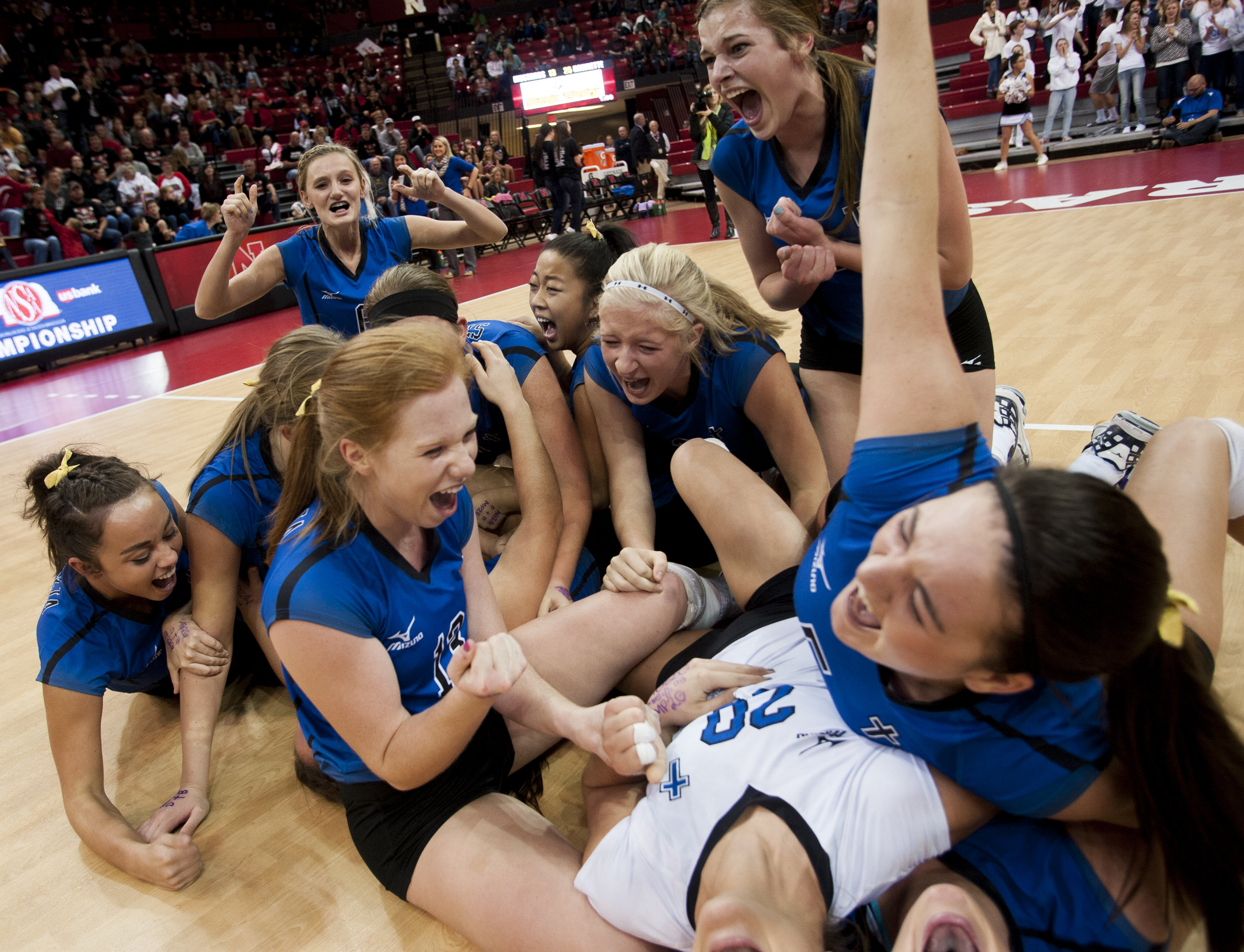 Hastings St. Cecilias' players dog pile at center court after defeating Stanton in three straight sets in the Class C-2 Championship game in Devaney Sports Center Saturday, November 14, 2015 in Lincoln.