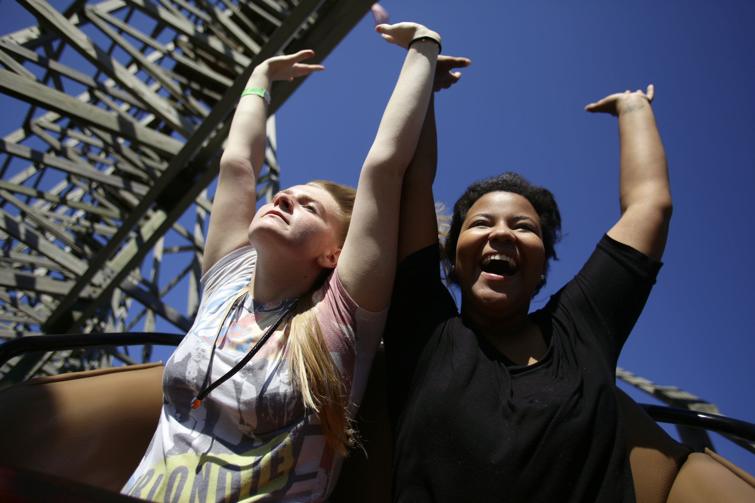"""Enjoying time off from work Bowling Green residents Kelcie Poteet, 17, and Jean Burden, 16, (L to R) throw their hands in the air while riding Beech Bend Park's infamous wooden roller coaster """"The Rumbler"""" Sunday September 14, 2014. """"We got off early today so we decided we would start ridin'"""", Jean said. """"This is definitely the best part about working here."""""""