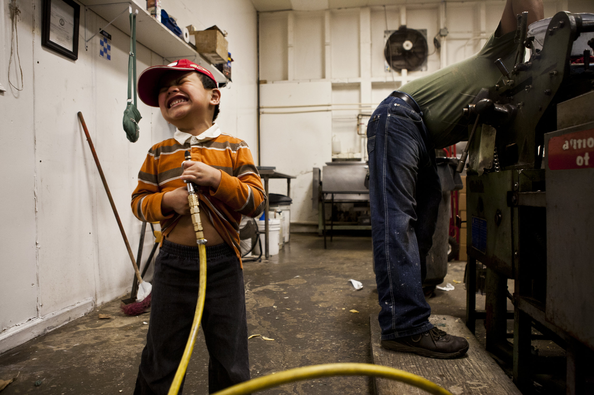"""While his father Roberto Valdez scrambles to clean the families tortilla shop, or """"tortilleria"""" in Spanish, at the end of a long work day Barzik Valdez, 4, amuses himself with an air compressor that is used to blow off dough from the machinery. Owner and operator of Tortillerias Provincia in Bowling Green, Ky., Roberto Valdez brought his family and talent for tortilla making from Mexico in 2009 searching for a better and more prosperous future. Barzik, the youngest of Roberto's four children, attends a local pre-school and is dropped off at the shop everyday around two in the afternoon."""