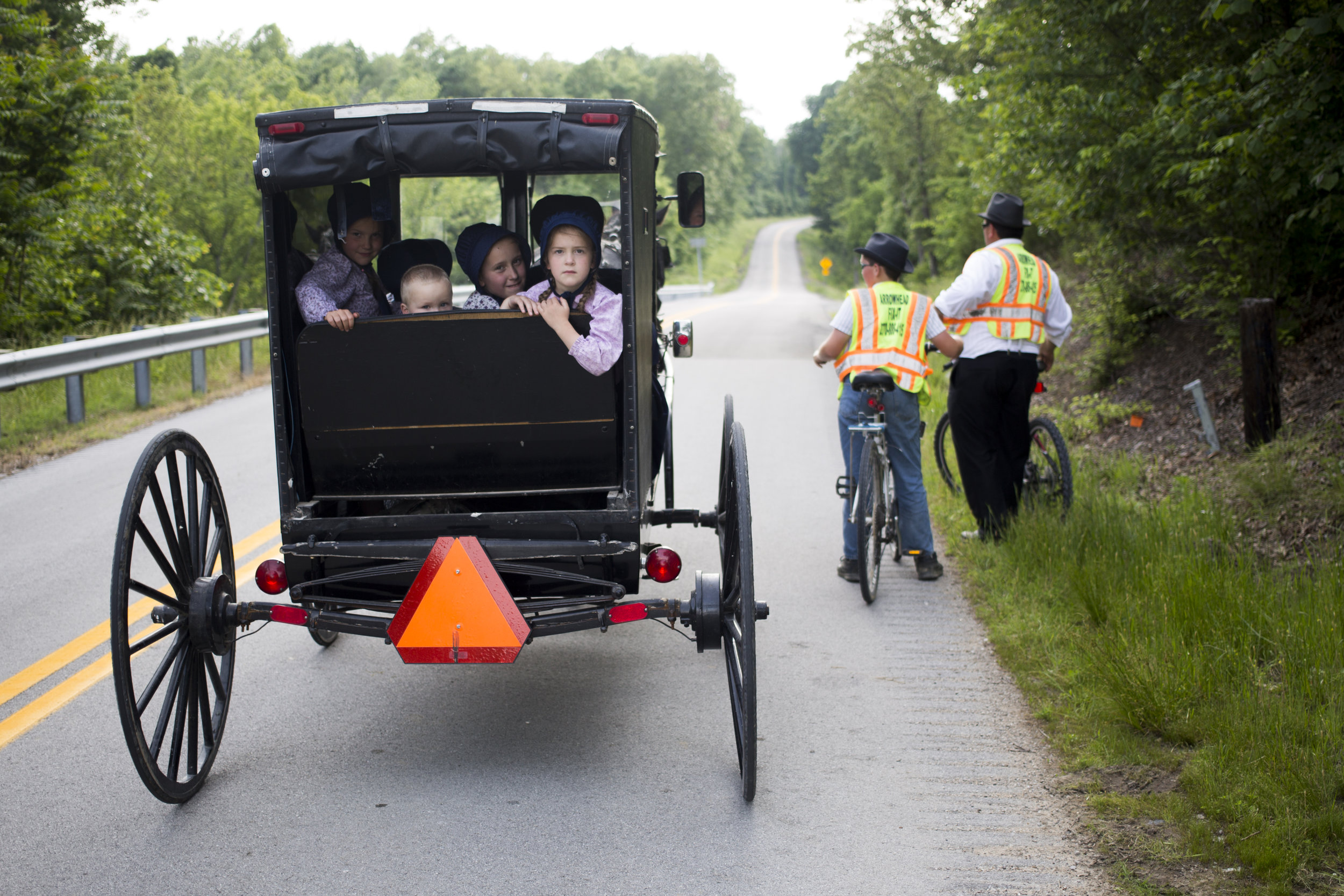 Filled with inquisitive stares from its passengers an amish buggy strolls casually down a country backroad outside of Hopkinsville, Ky. 2015.