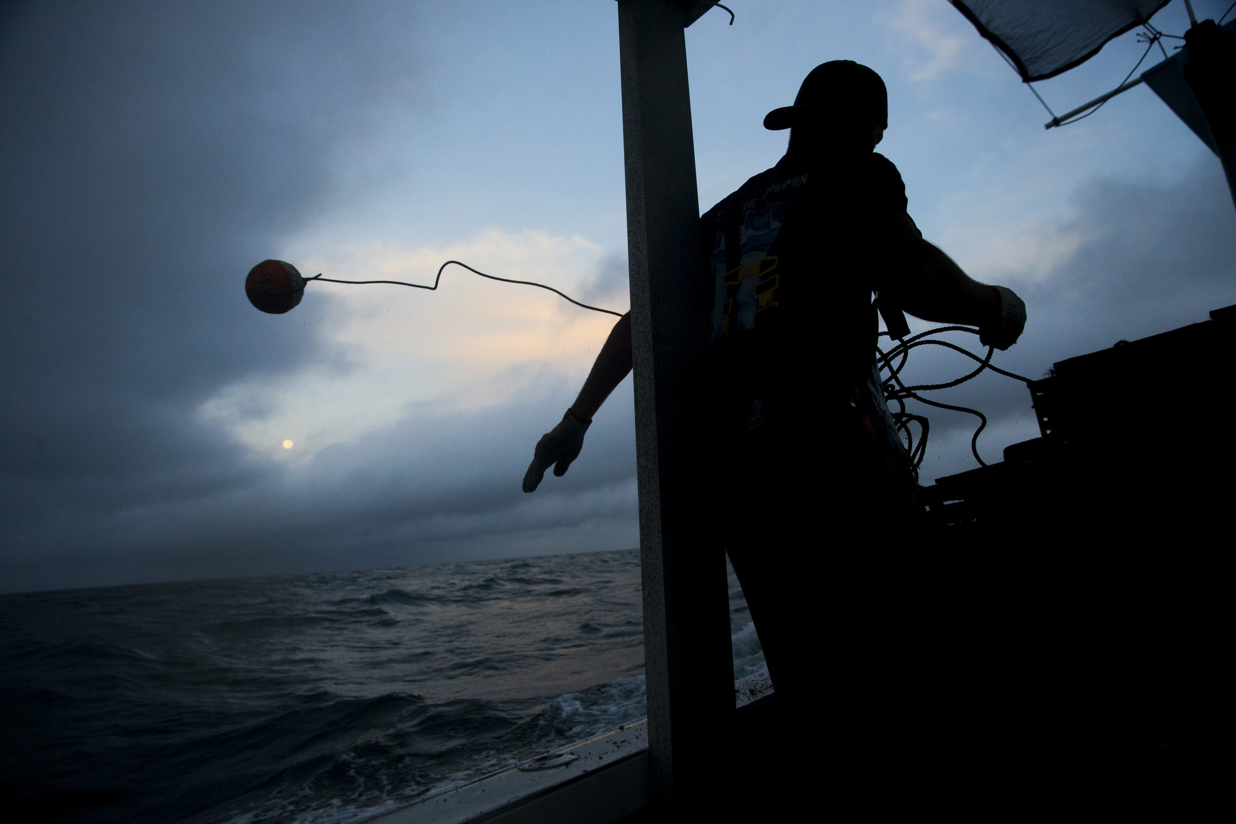 Tyler Few, crew member of the Miss Chloe Ann, tosses out a buoy to mark the location of a specific crab trap while running a line early Friday, October 6, 2017 off the coast of Goodland, Fla. During any given trip the crew will setup 200-plus traps. Open season for crab begins Oct. 15, 2017.