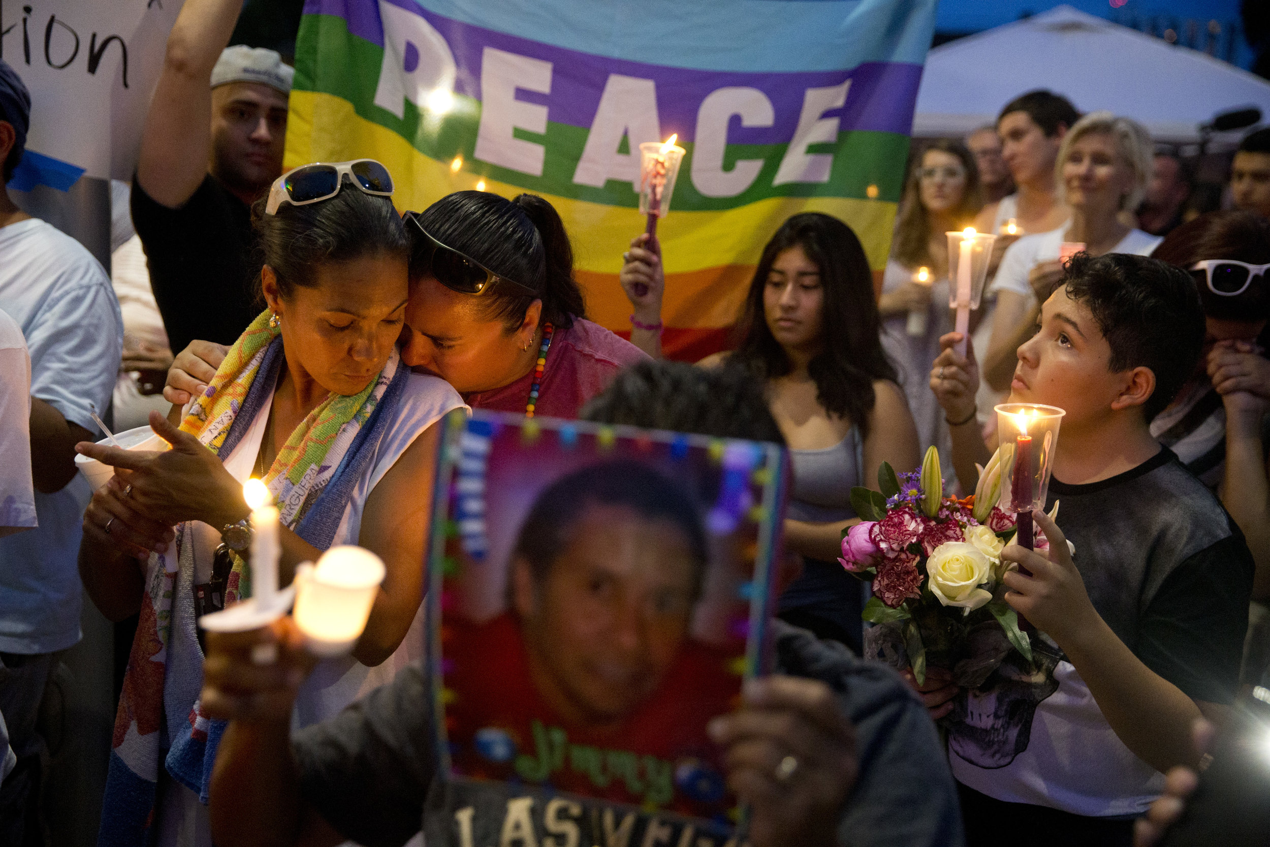 """Jessie Perez, far left, nuzzles against her girlfriend Gina Travez, left, as church bells are rung 49 times for the 49 victims of the Orlando Nightclub shooting at the Dr. Phillips Center for the Performing Arts Monday, June 13, 2016 in Orlando, Fla. """"This is our home,"""" Jessie said. """"That's why it hurts so much."""""""