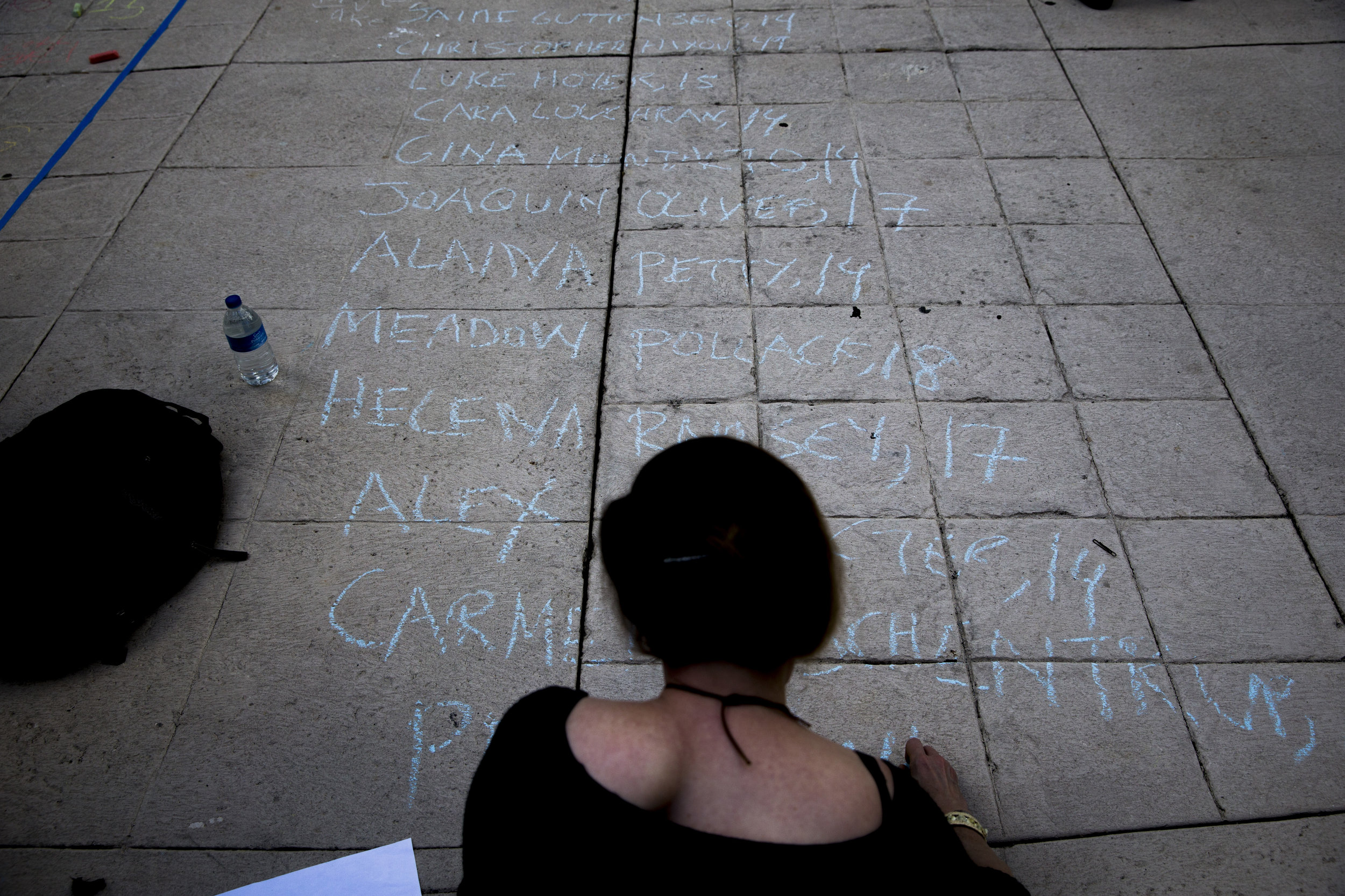 Hester Kamin, a long-time arts and humanities educator, marks down the names of the 17 lives lost in the Parkland, Fla. mass shooting at Marjory Stoneman Douglas High School outside the Collier County Courthouse Friday, Feb. 23, 2018 in Naples.